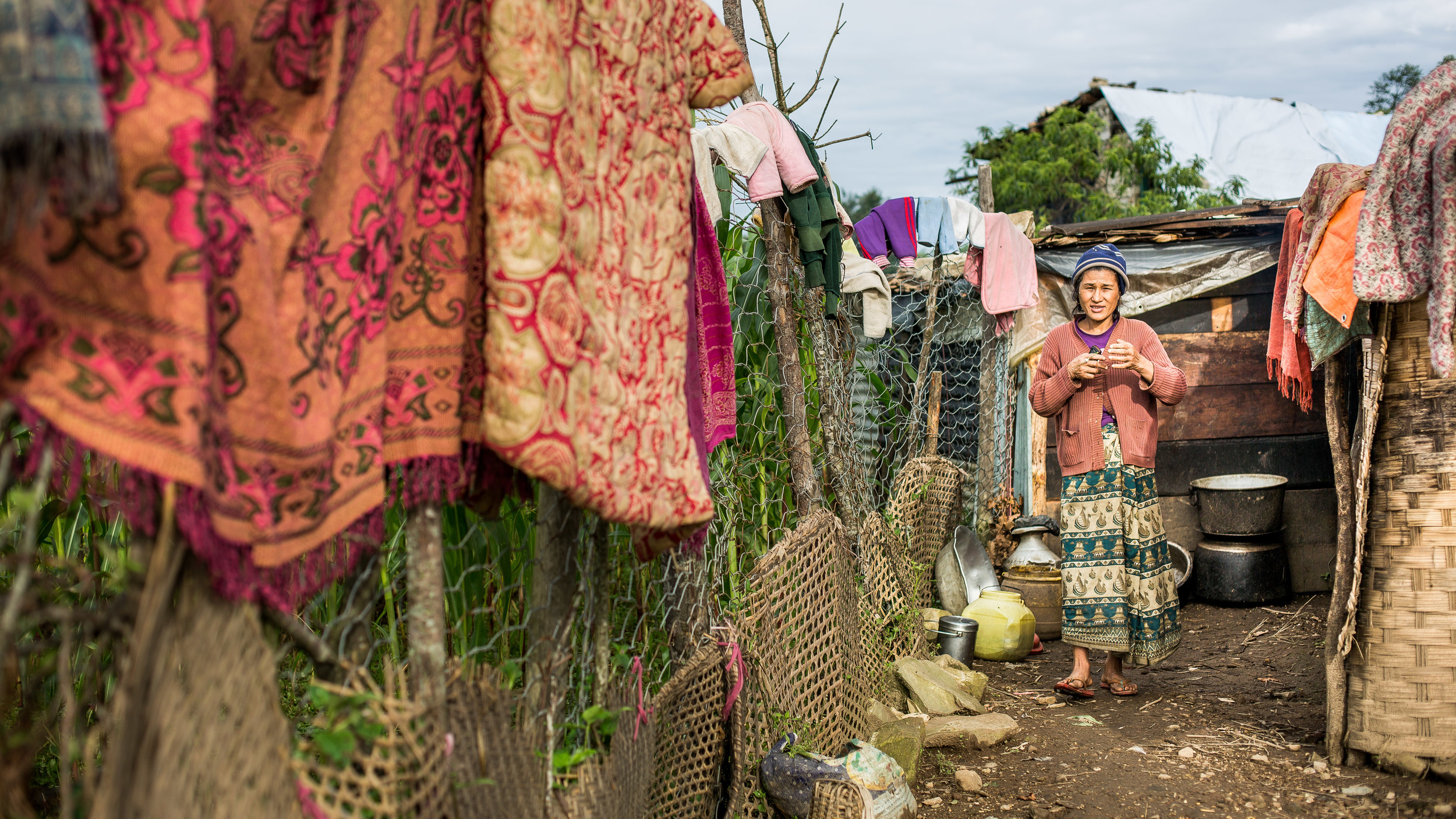 Women living in her plastic shelter that is too small to store all the family clothing and blankets.