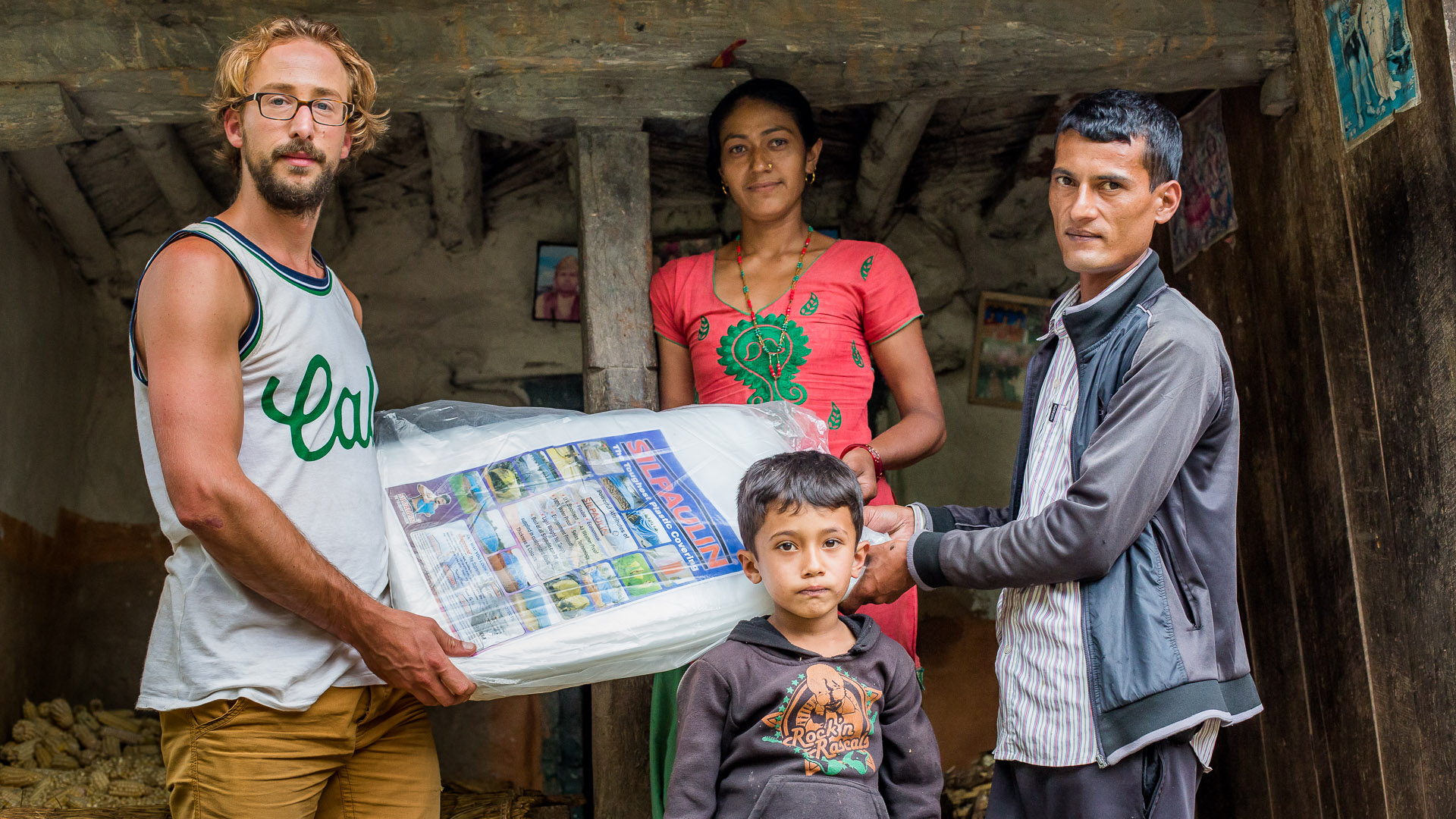 Handing over one of the plastic sheets to a teacher and his family.