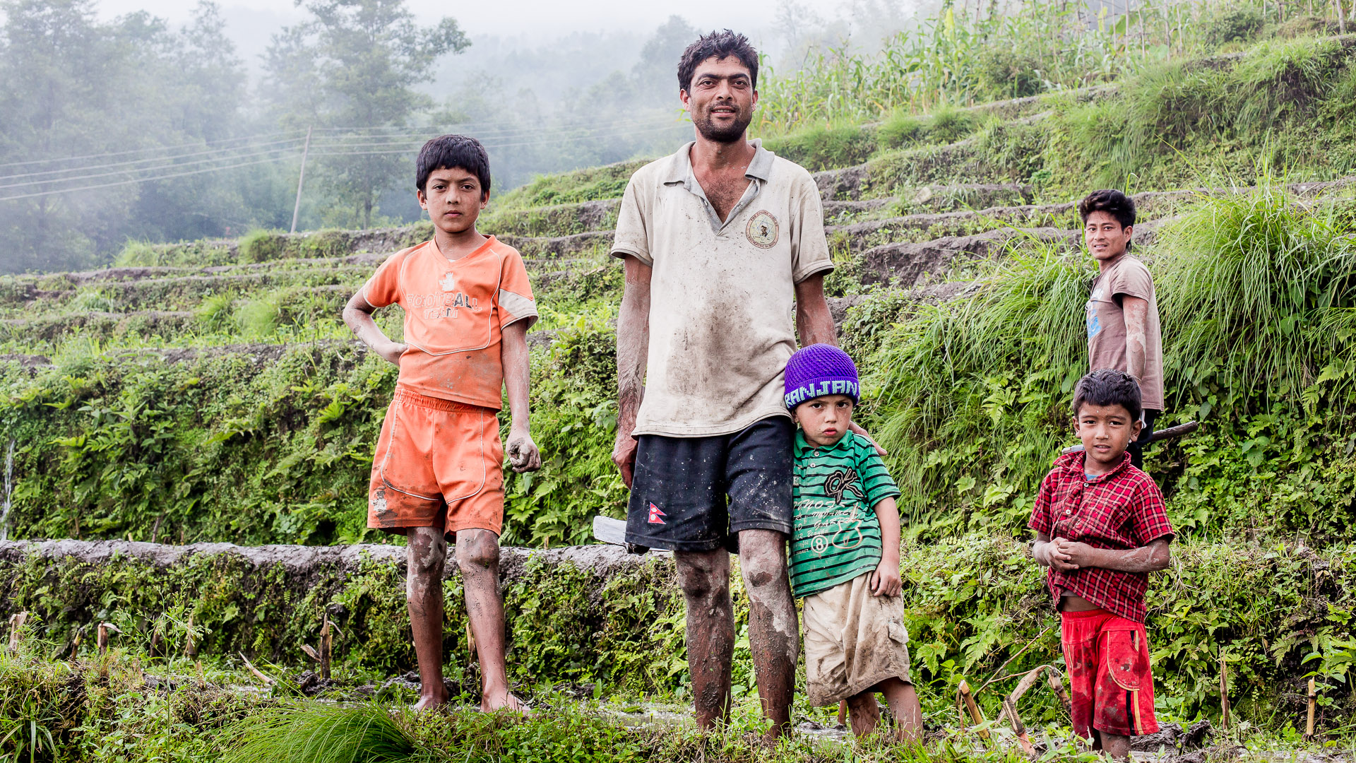 Dili Bastola posing with his children while working on his fields. Dili is starting a fish business by creating a fish pond just bit lower on the mountain.