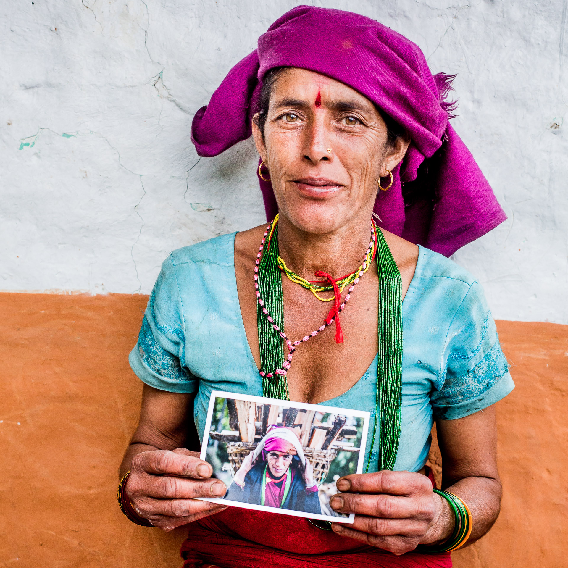 Posing with her photo wearing traditional clothing. The yellow and green necklace and the bracelets on her arm signify that she is married.