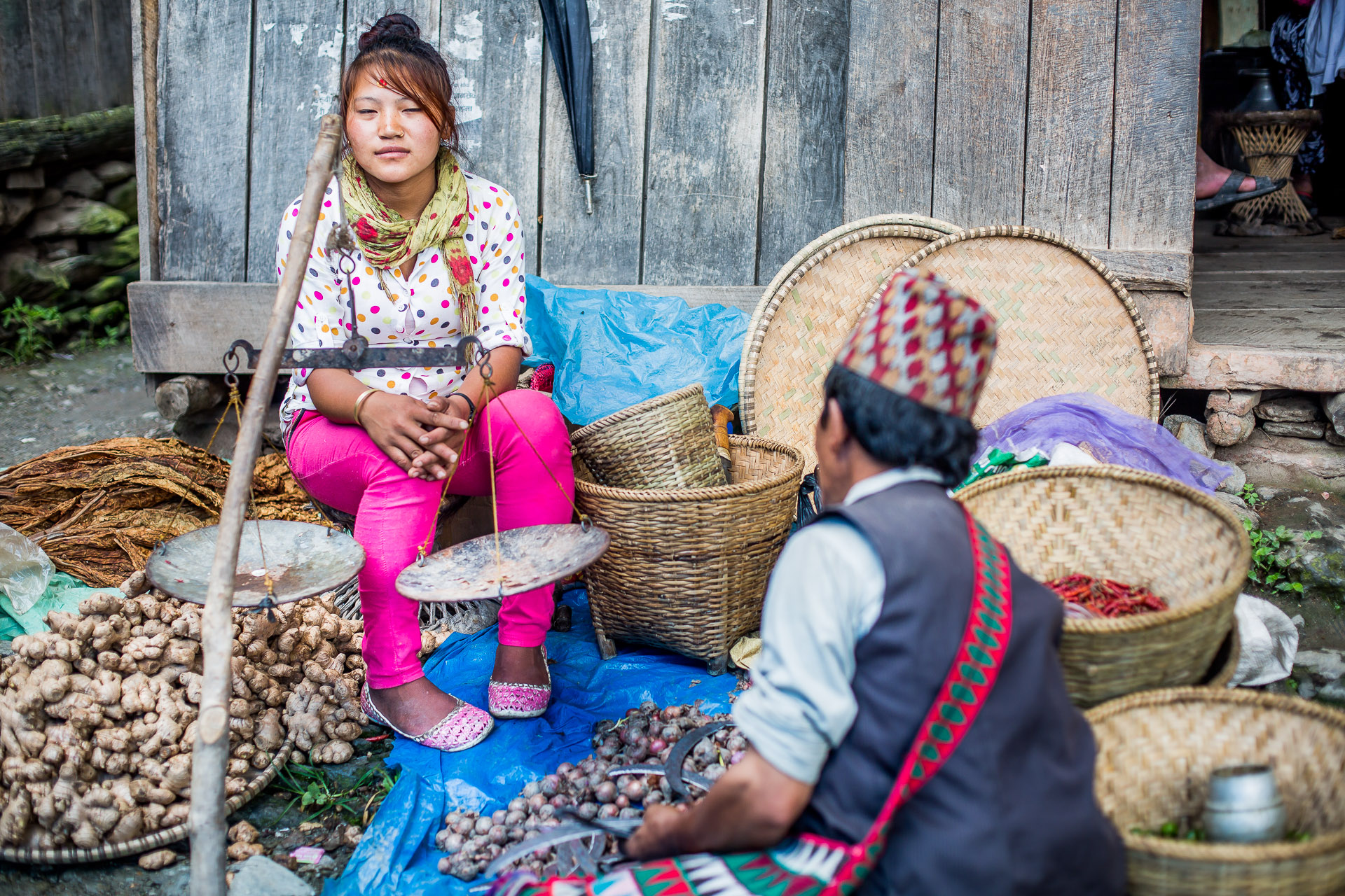 Girl selling onions, ginger and tobacco leaves.