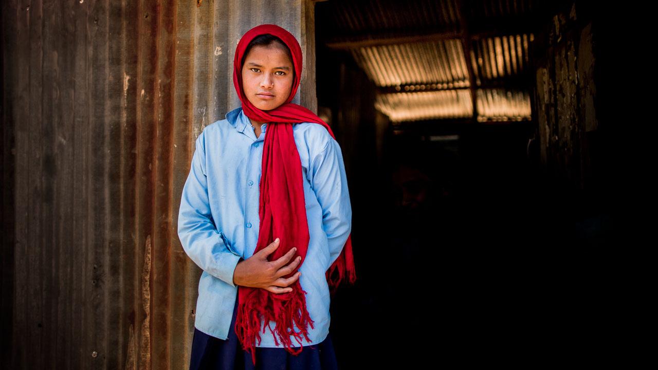 Girl standing in front of her temporarytinclassroom.