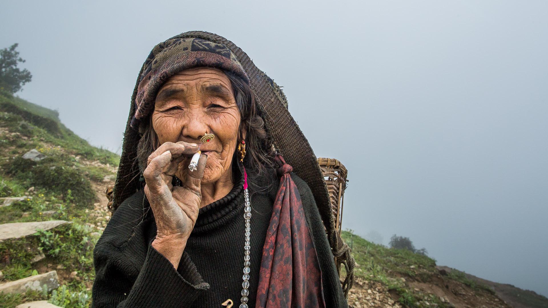 Gurung lady smoking a cigarette.