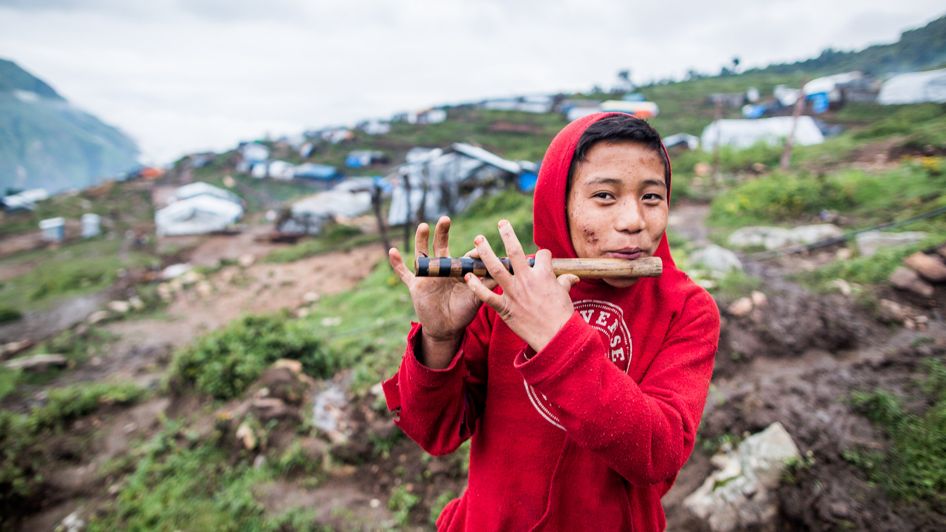 Boy playing his traditional Gurung flute just before sunrise.