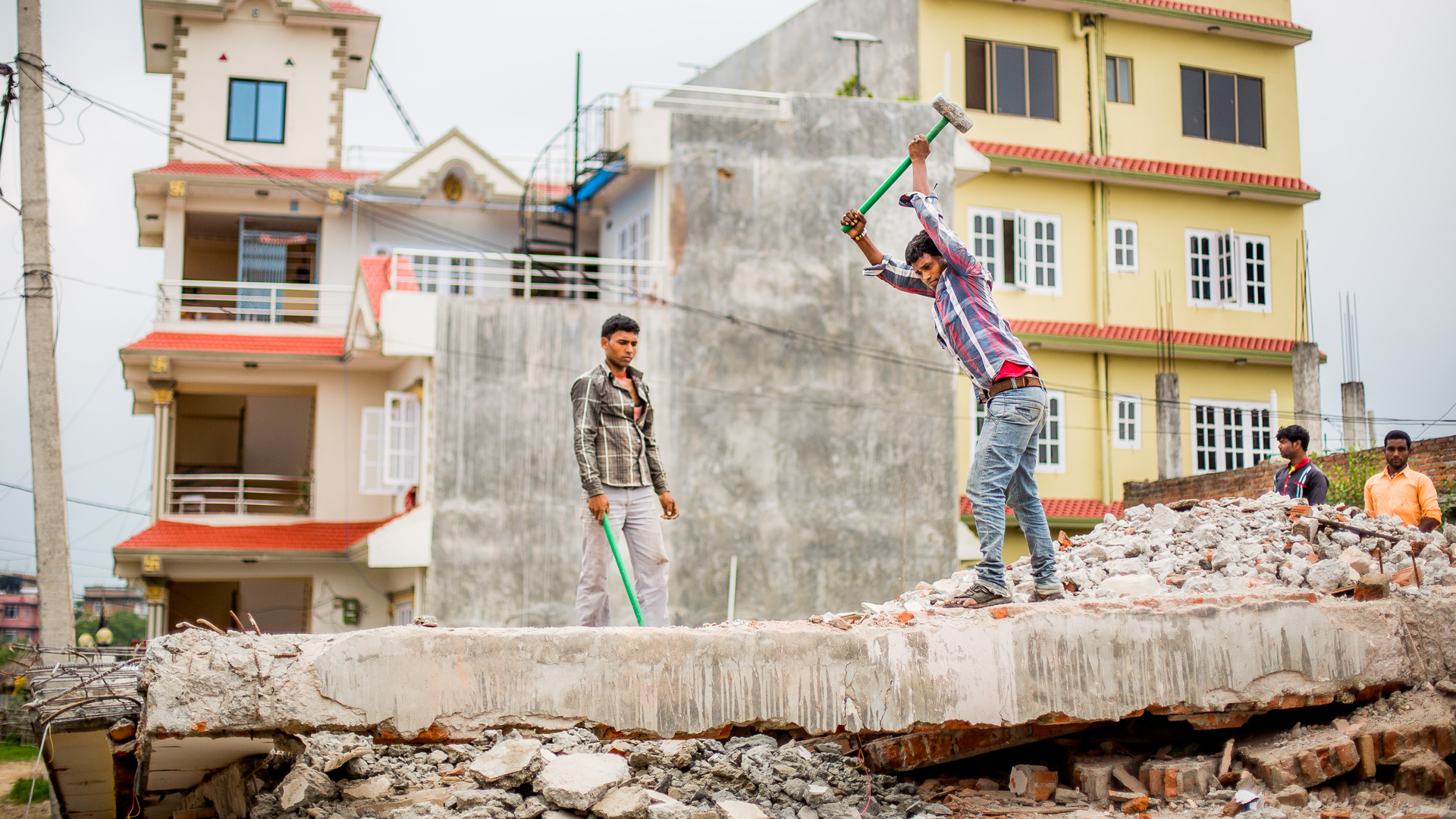 Demolishing concrete floors by hand that had collapsed during the earthquakes.