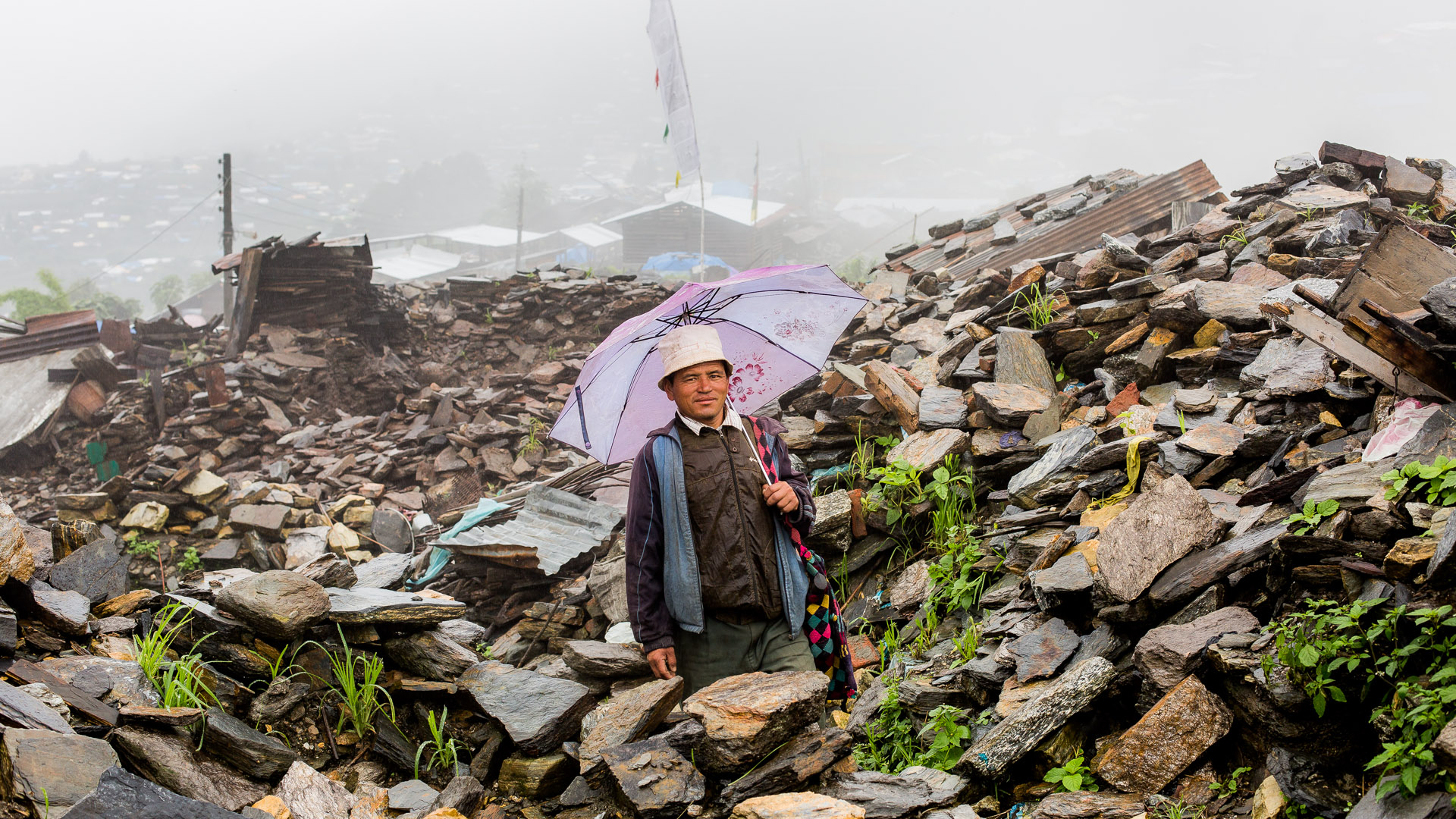 Villager of Barpak walking around in the area where their village was and now is a warbled of ruins.
