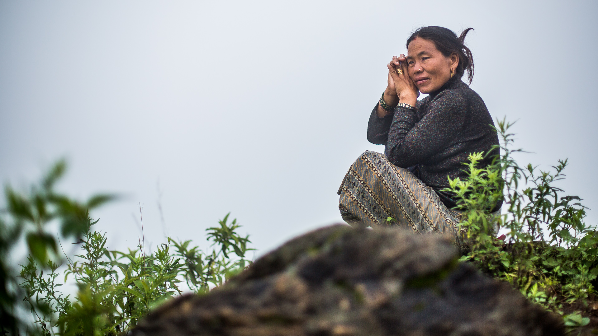 Lady who lost her house and family  looking over the valley thinking about past and future.