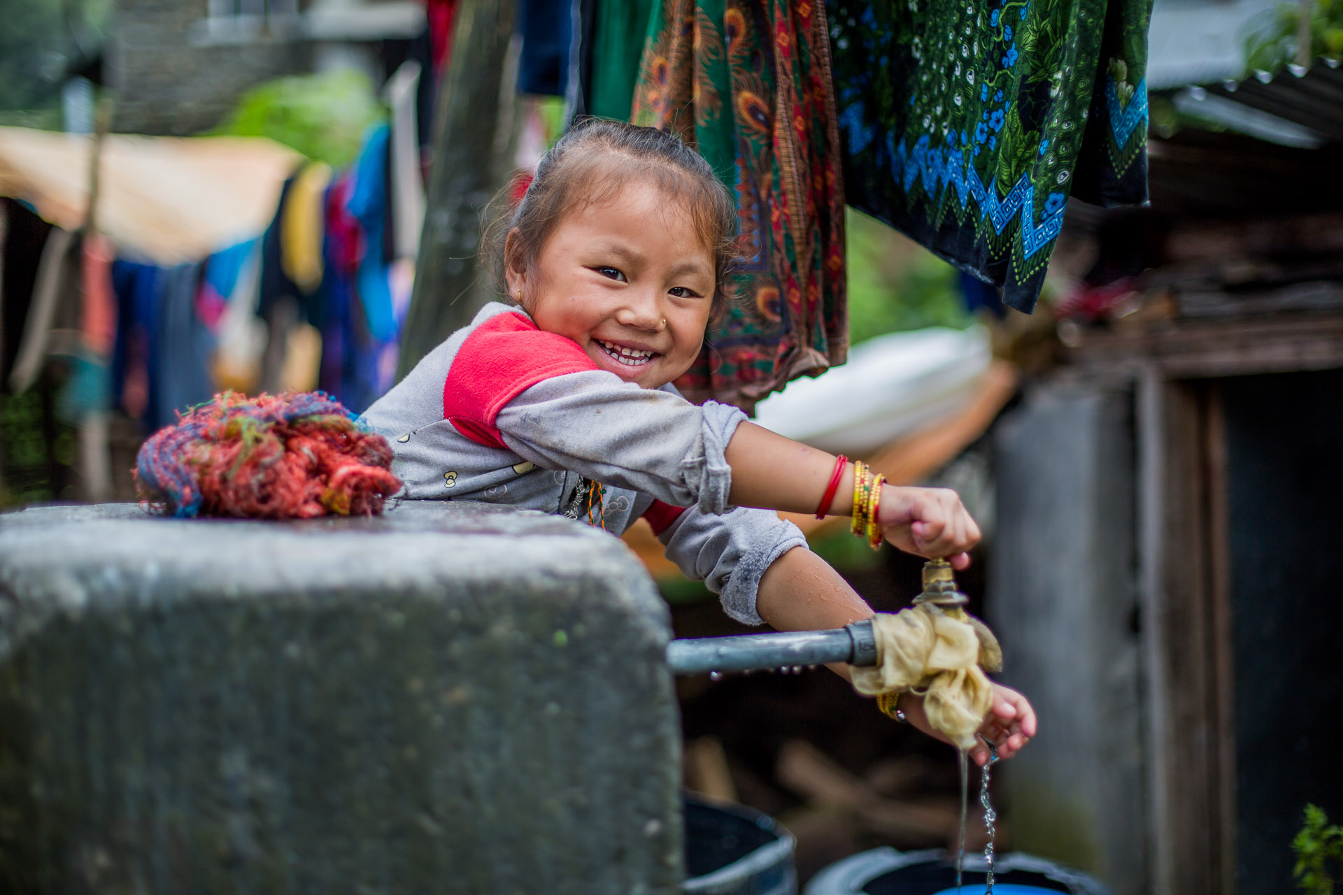 Girl having fun playing with the village water tap.