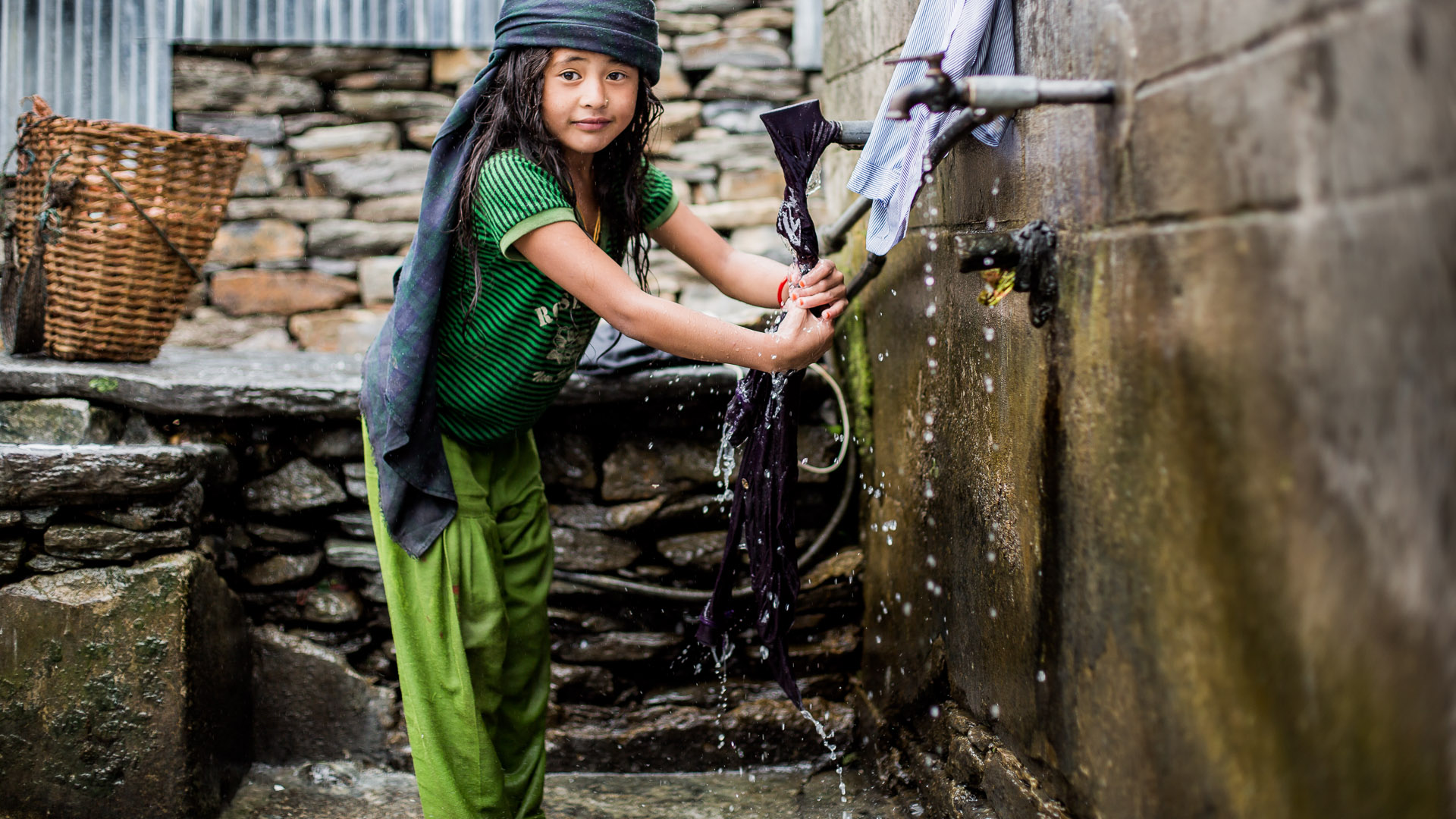 Young girl washing her clothes at a local water tap. Girls are usually helping from very young age in all housekeeping, cleaning and cooking.