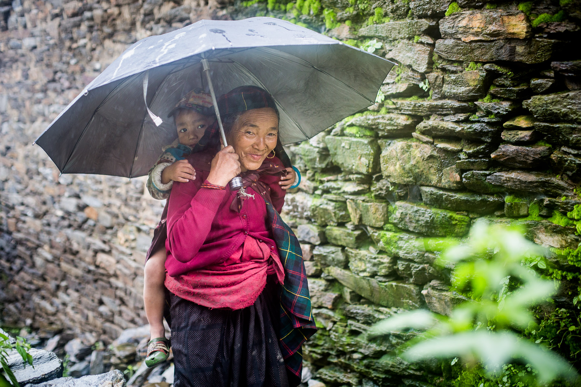 Grandmother with her grandson walking on their way to the ruins of old Barpak.