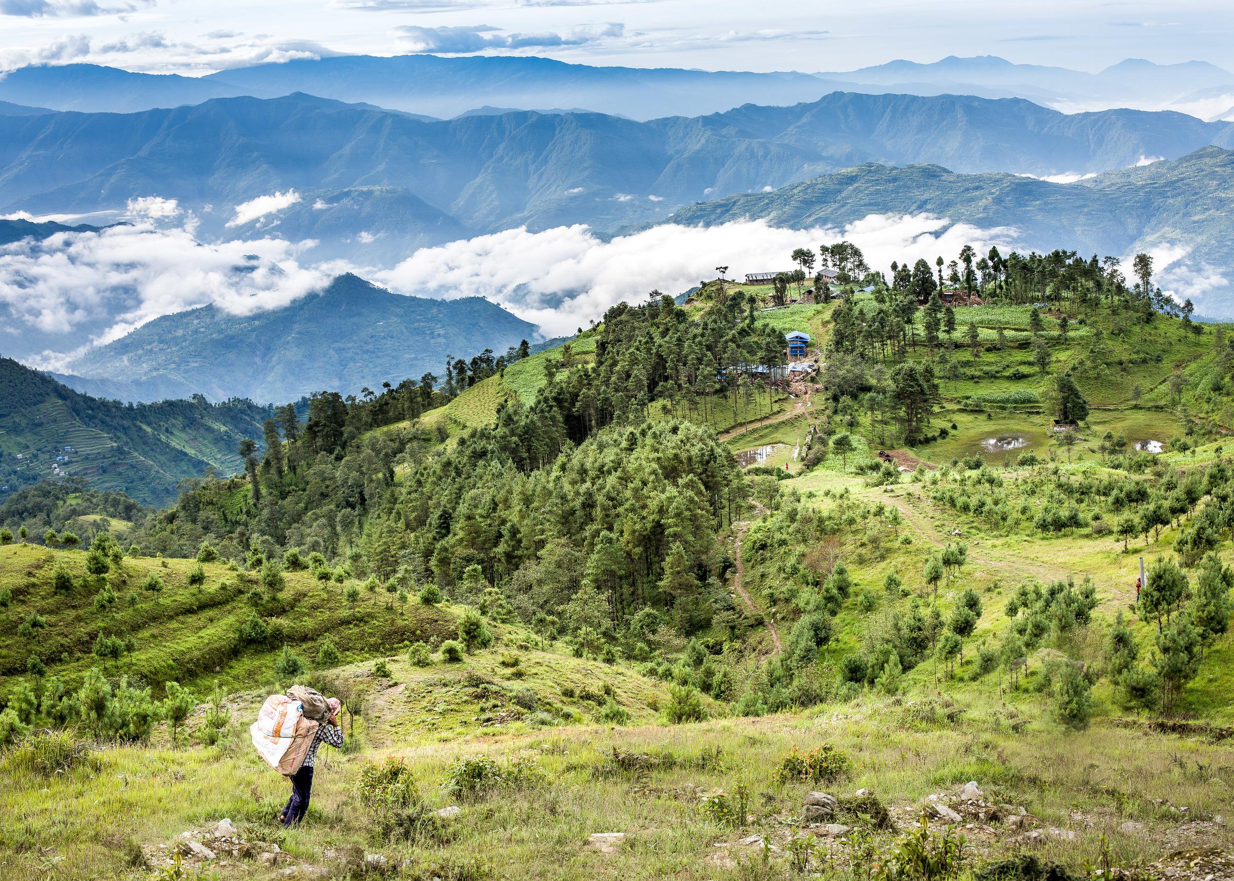 Onze drager die tijdens onze voorbereidende reis op weg is naar het op de heuveltop gelegen plaatsje Deorali.