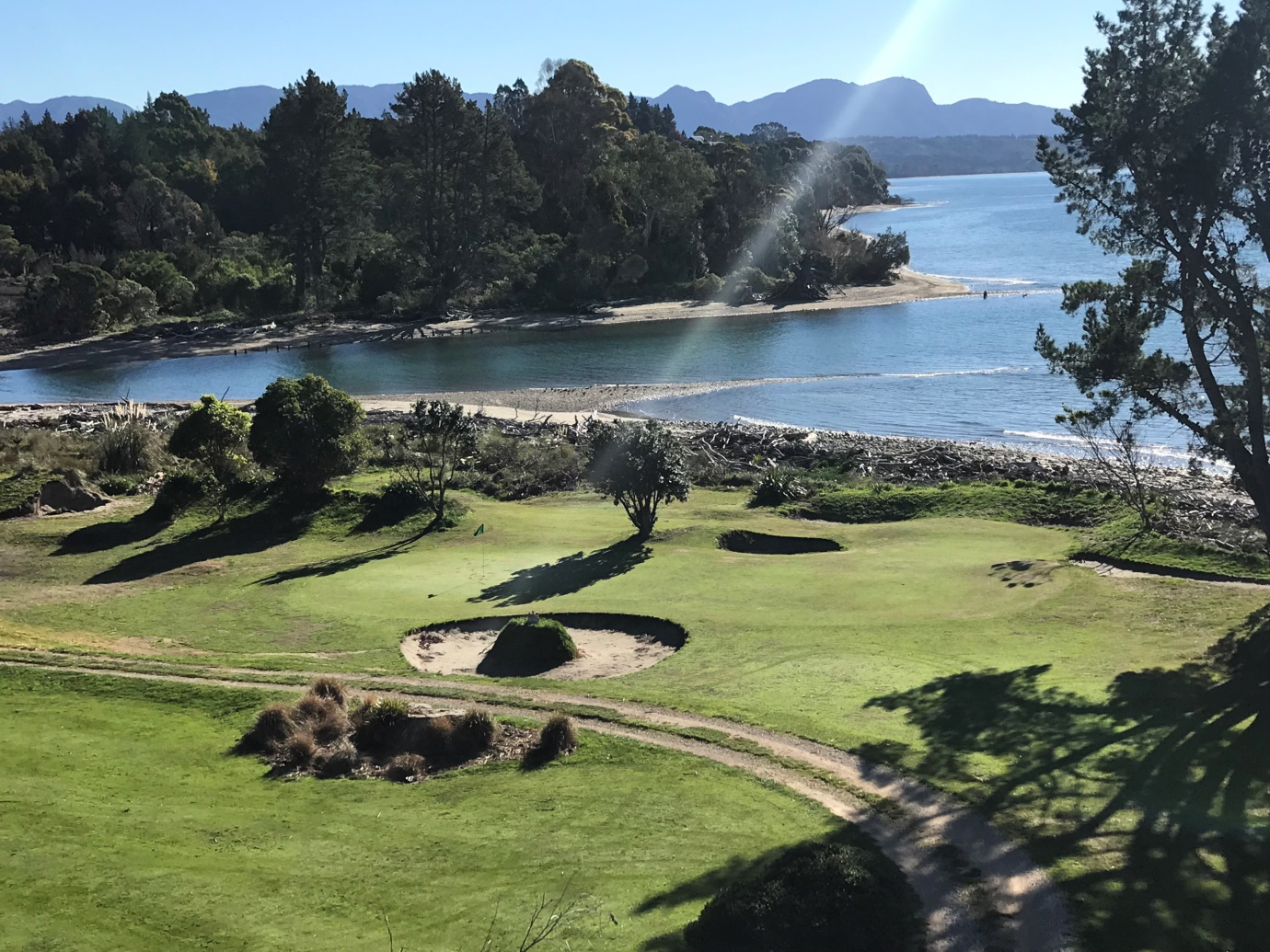 The 12th green – surrounded by 5 bunkers and ocean behind