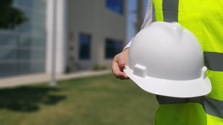 Construction workers in a reflective vest holding white hard hat.