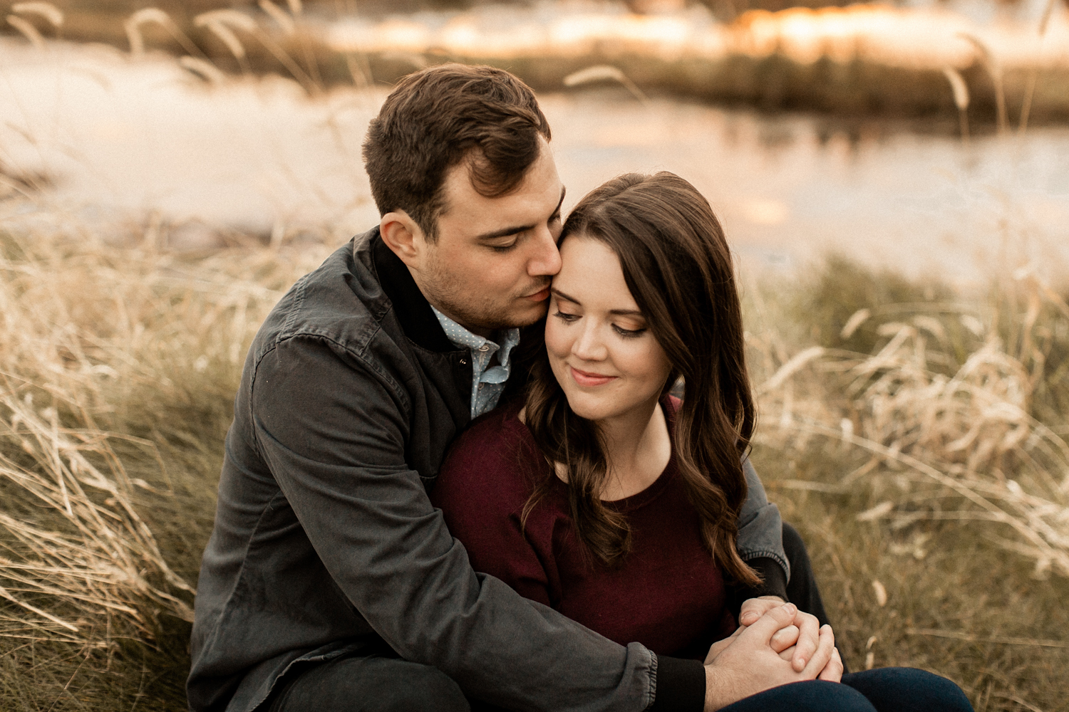 Snuggled up couple at outdoor fall engagement photoshoot