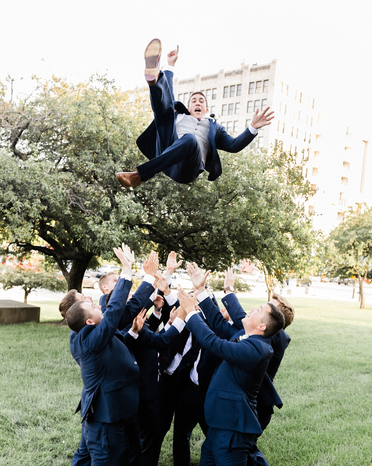Groomsmen toss Groom in the air in downtown Indianapolis, IN wedding picture.