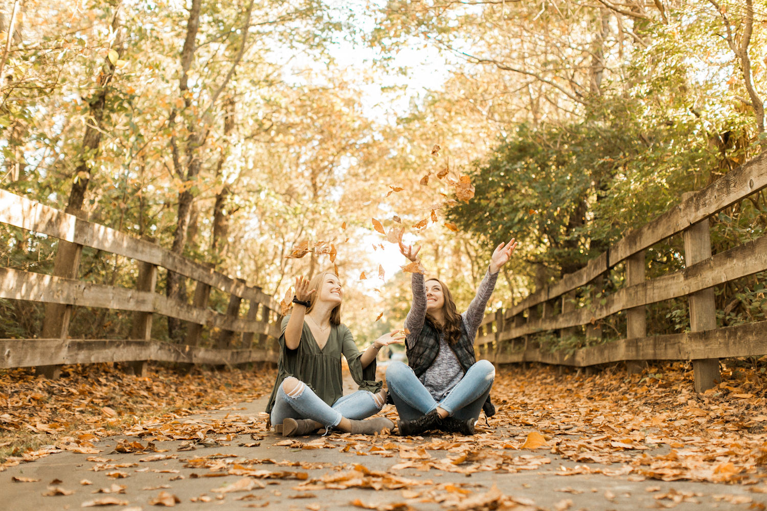 High school seniors throwing leaves at fall photo shoot in Indiana