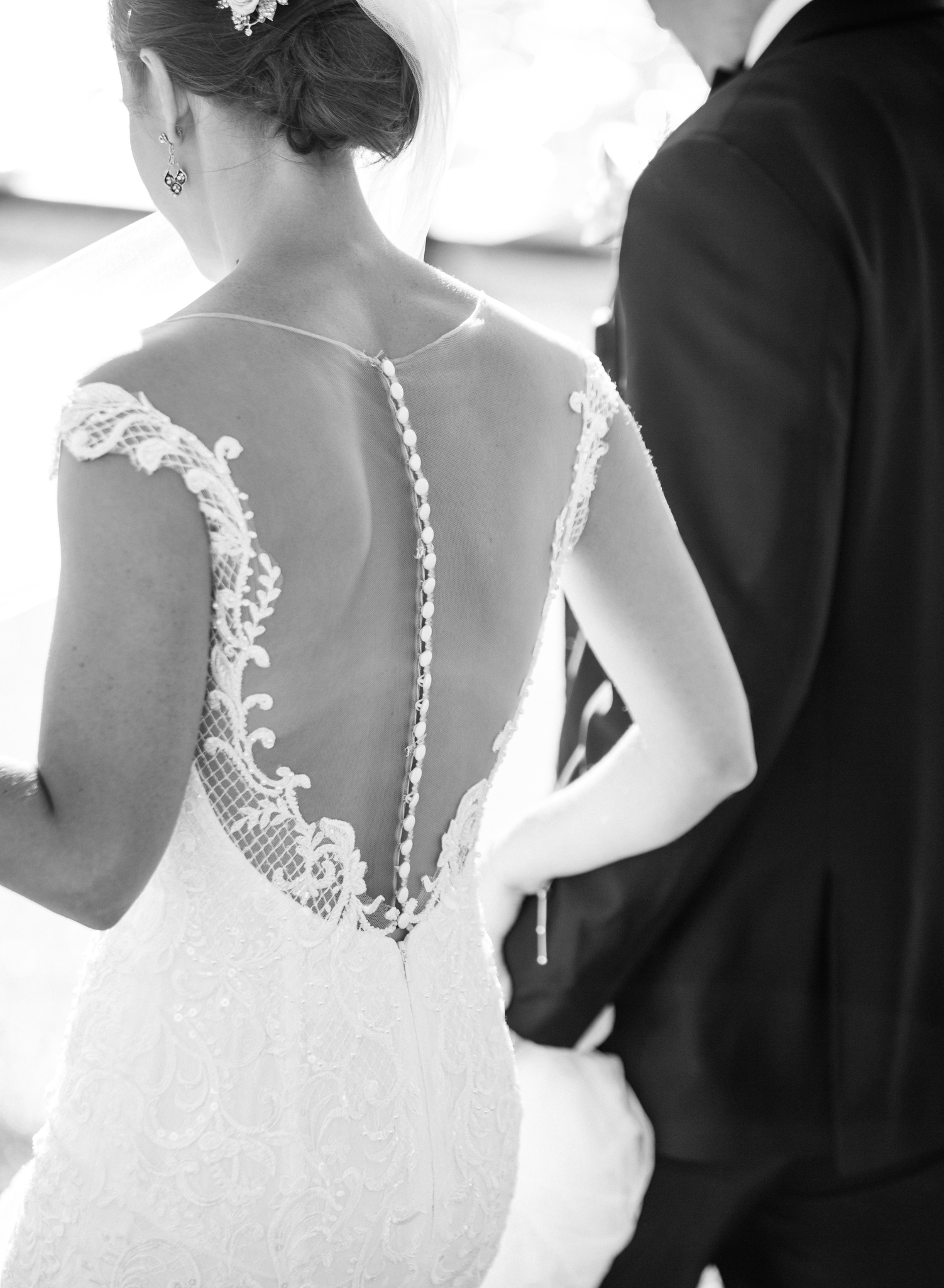 Bride & Groom Walking in Downtown Chicago with lace open back button up wedding dress