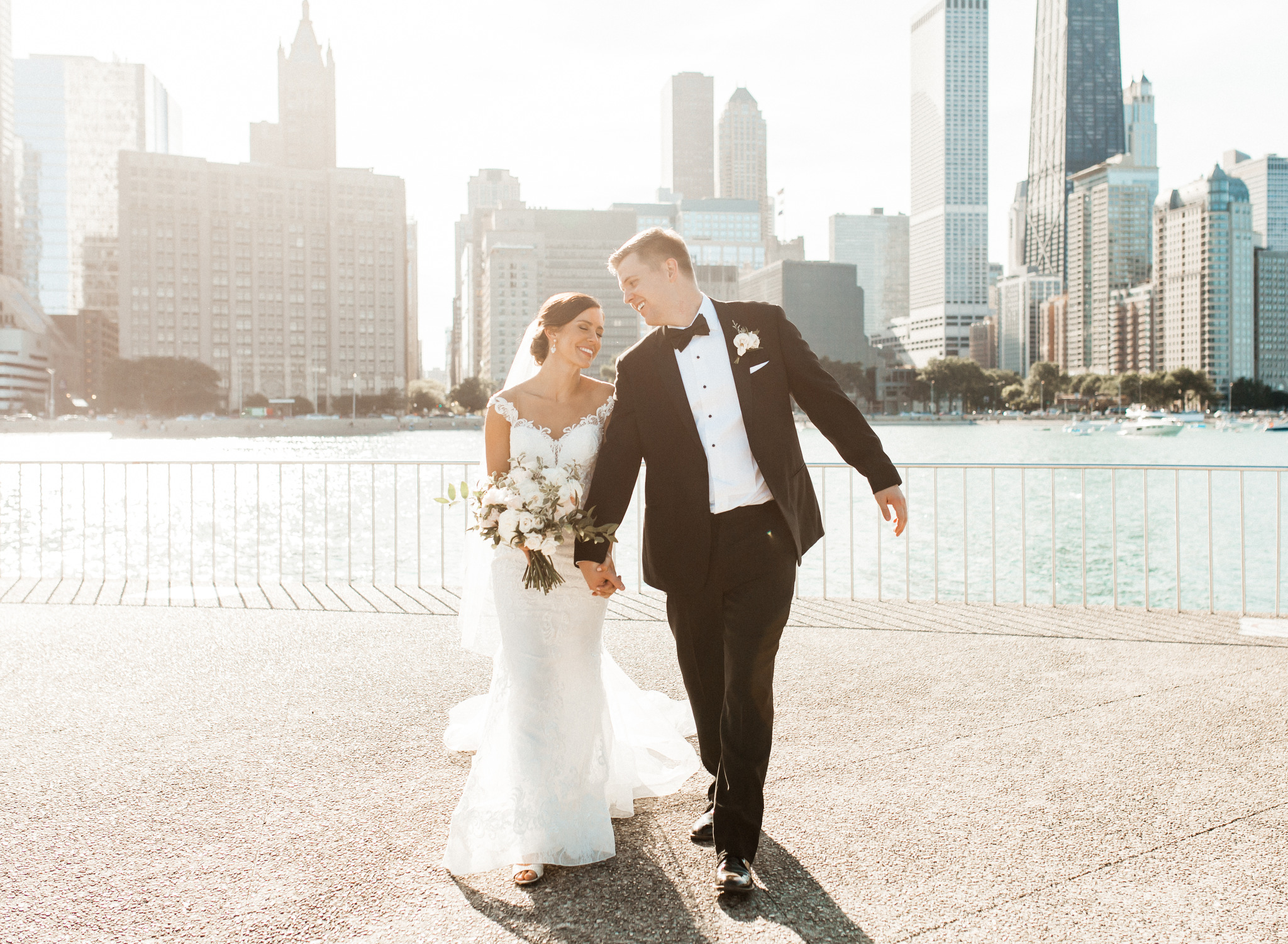 Bride & Groom walking and laughing in front of Downtown Chicago Skyline at Milton Olive Park with Wedding Photographer