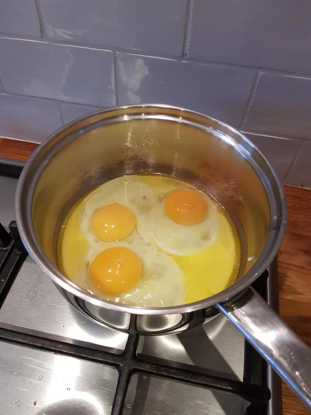 2: Start to cook the eggs in the butter.