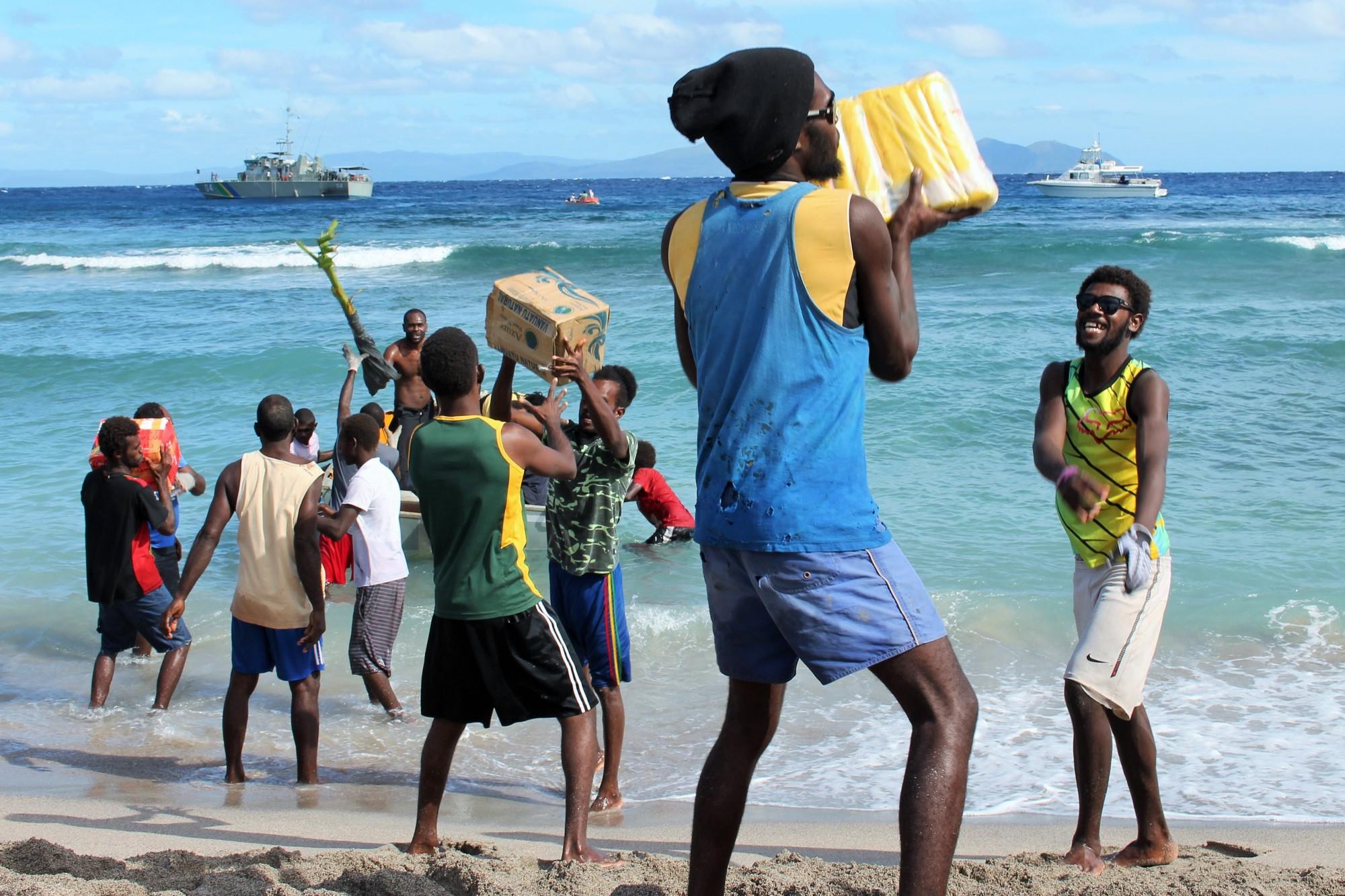 Community Members unloading food supplies and NFI kits in Mataso Island, Vanuatu (Alberto Preato /IOM)