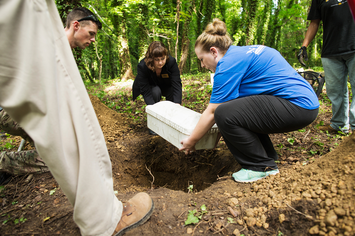 Workers from the Nelsen Funeral Home reinter remains with the assistance of regular cemetery cleanup volunteers from the Friends of East End.