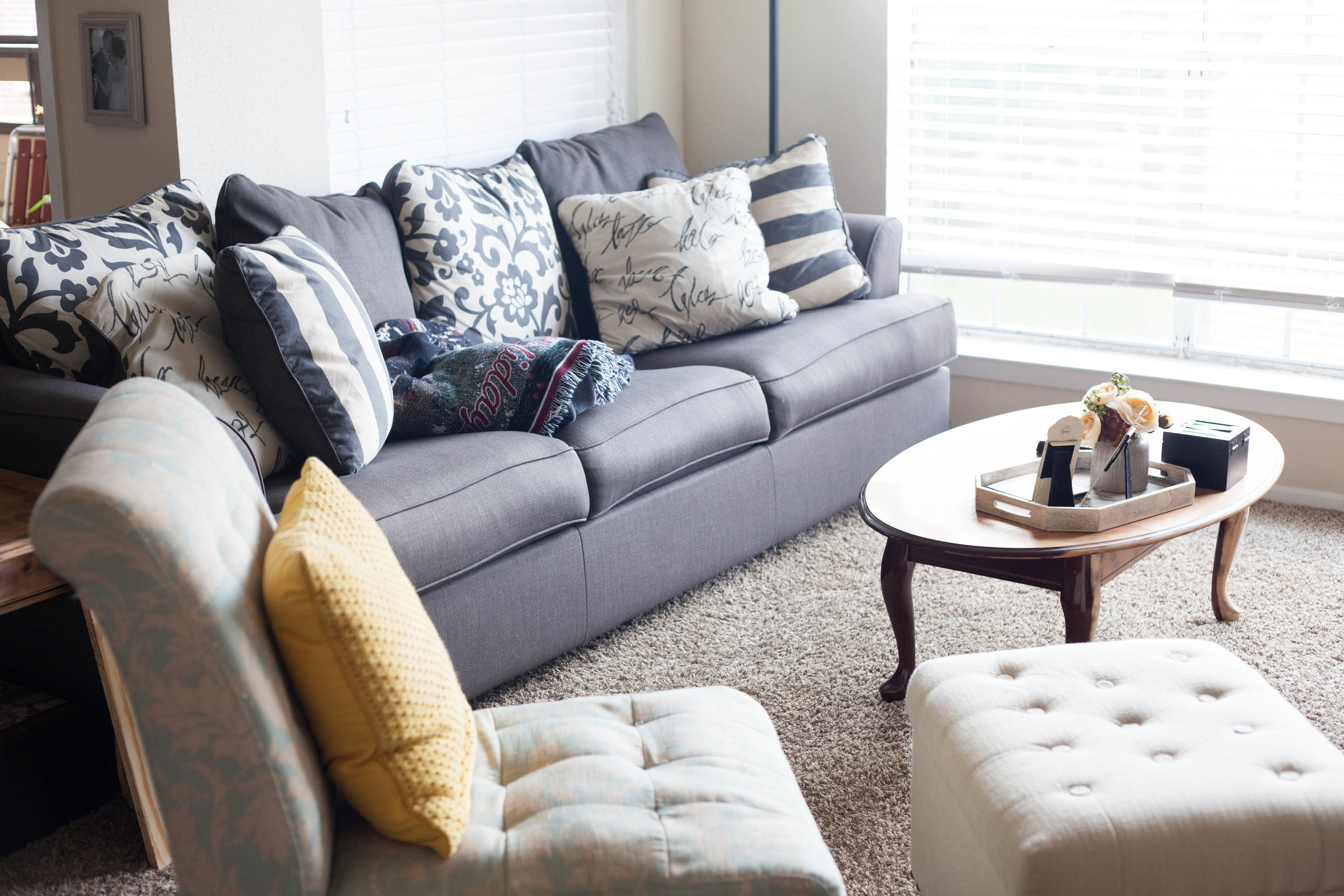 """Couch:  Ashley Furniture  Ottoman:  Target  Yellow pillow:  Target  Flowers:  Michael's  Table: Hand-me-down from my parents, Cory sanded it to get the worn look. Tray: Was a birthday gift. Probably from Kirklands or something! """"M"""" box: Hand-me-down from my mother-in-law."""