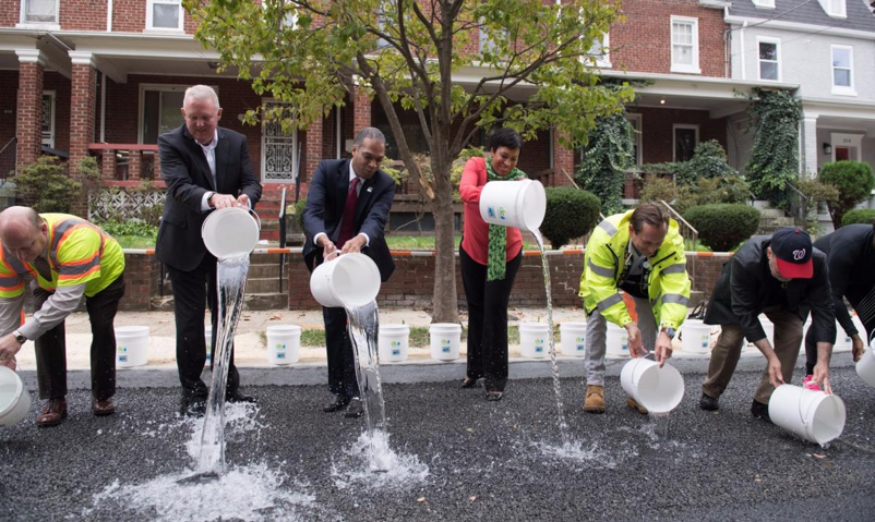 DC officials celebrate the groundbreaking of a green infrastructure project financed by an Environmental Impact Bond.