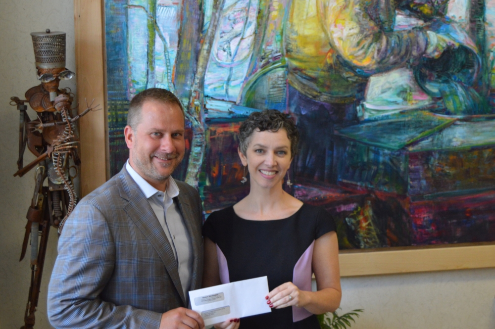 Resch Strategies president Matt Resch presents the scholarship check to Lansing Art Gallery director Barb Whitney