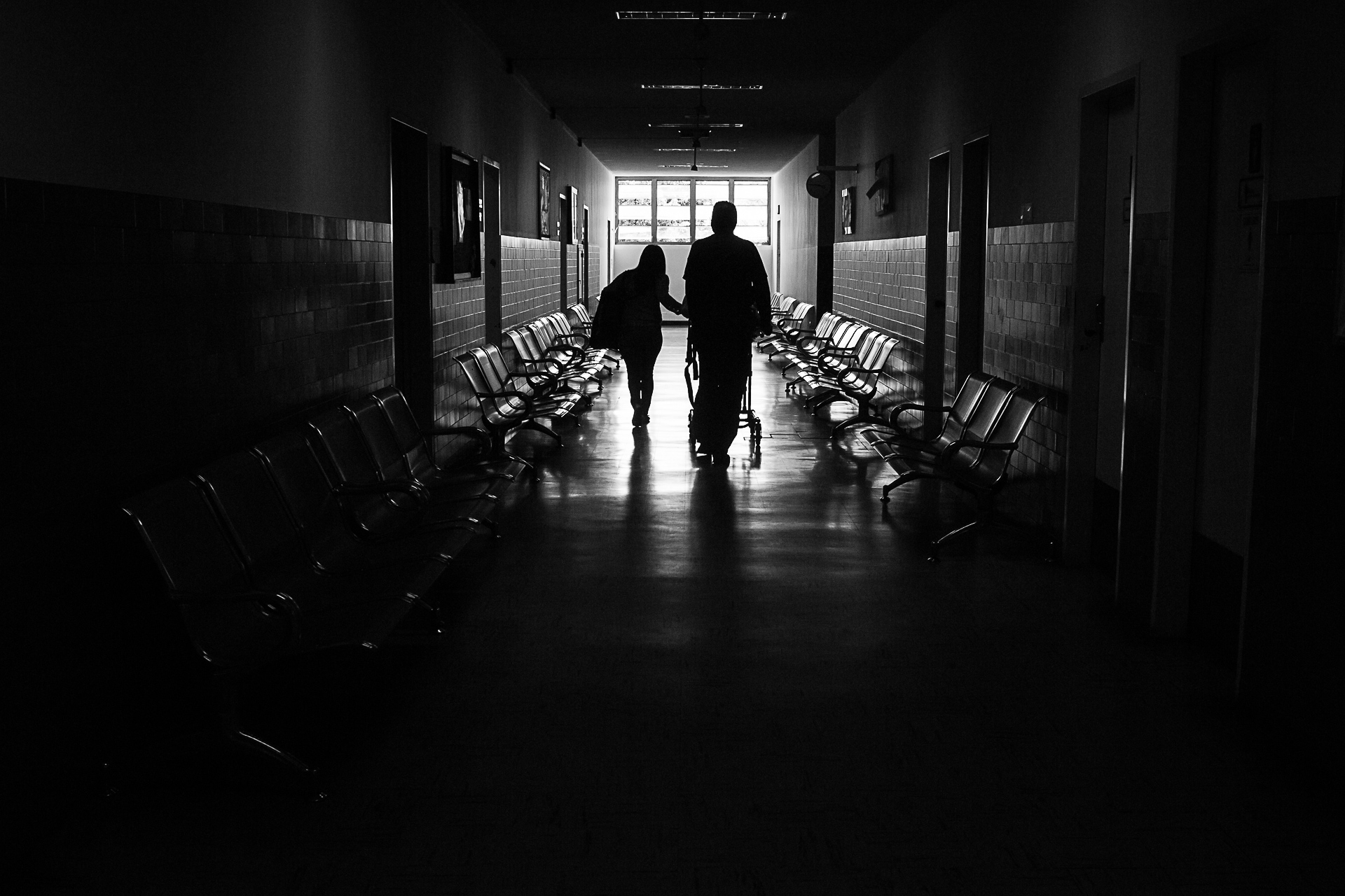 His mom and doctor walk with him on a stretcher through the hospital's hall.