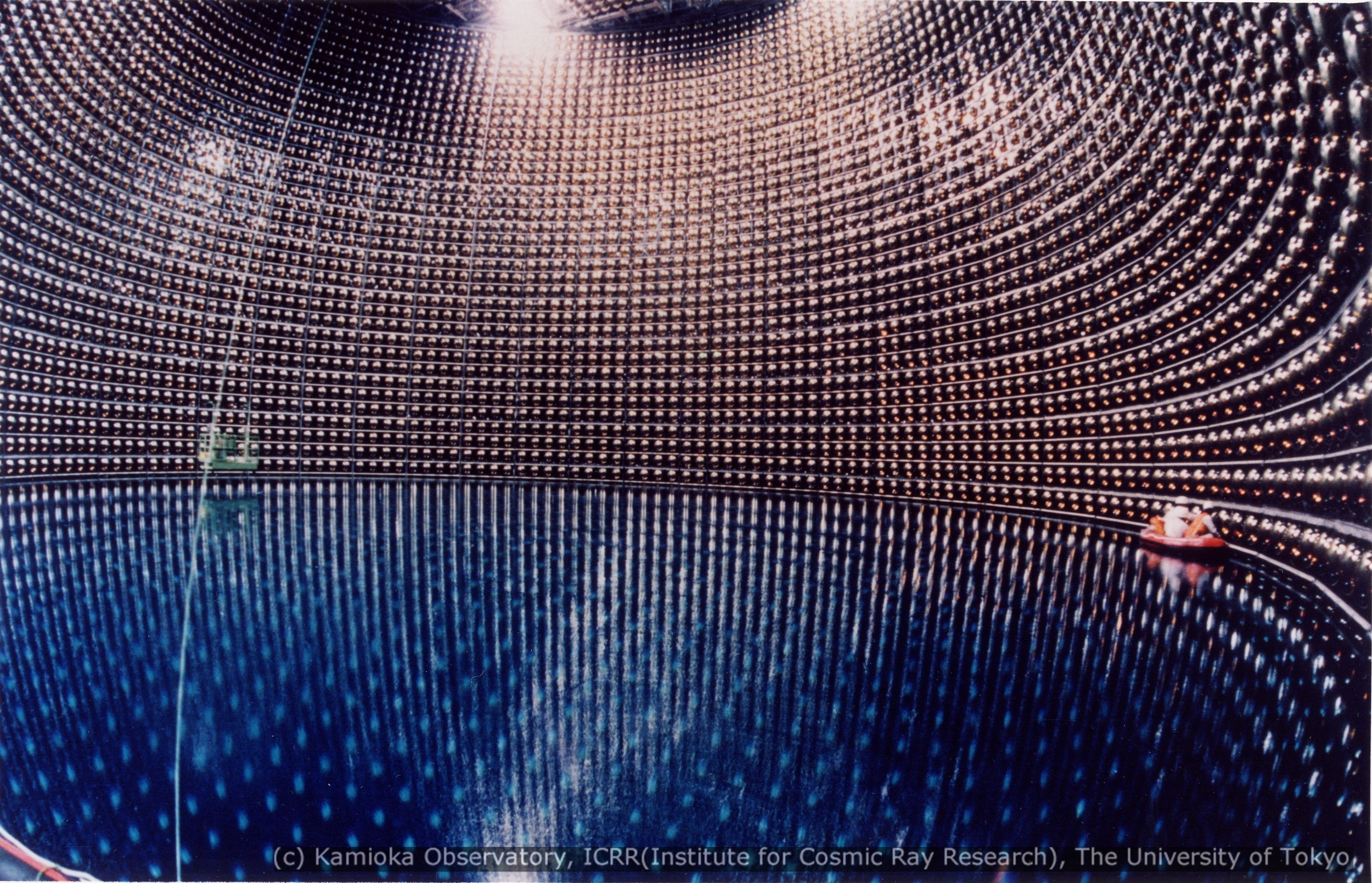 Super-Kamiokande (the follow-up experiment to Kamiokande) being filled with water in 1996, with technicians cleaning the photomultiplier detectors