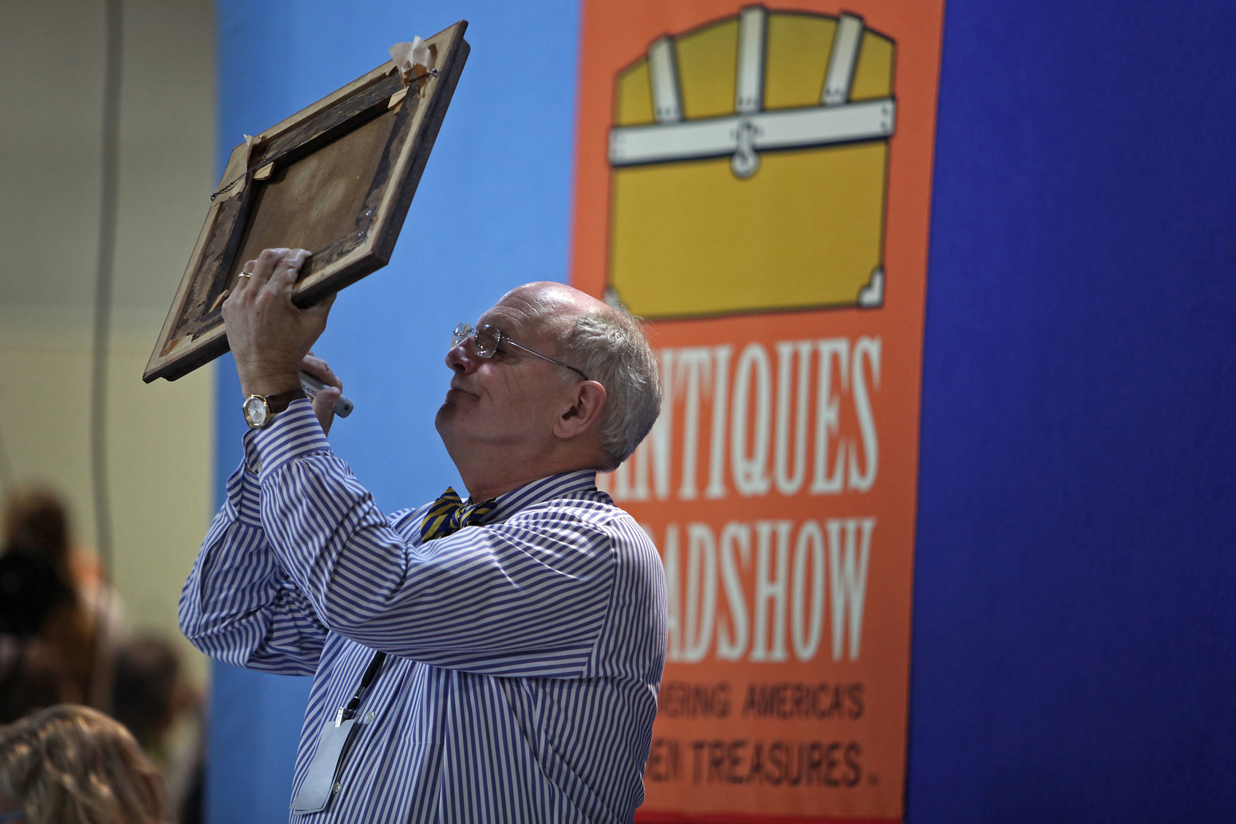 Appraiser Peter Fairbanks looks at a painting with UV light to see if the signature was added to the painting later at the Antiques Roadshow at the Albuquerque Convention Center, July 19, 2014, in Albuquerque NM. (Morgan Petroski/Journal)