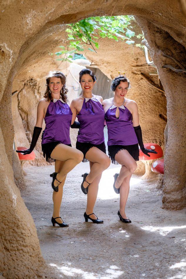 three girls in purple top with leg raised to knee