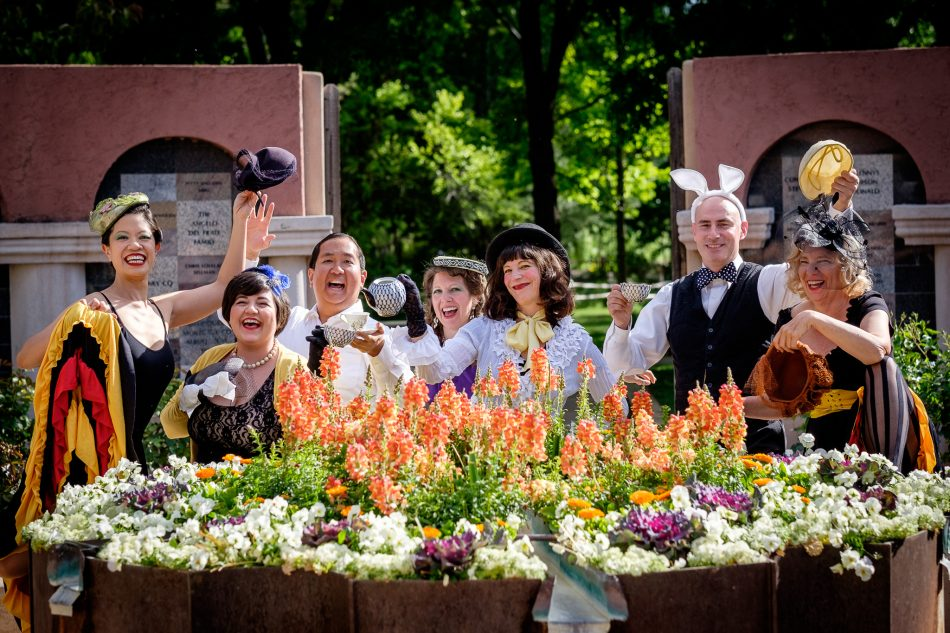 cast of alice in jazzland around table of flowers