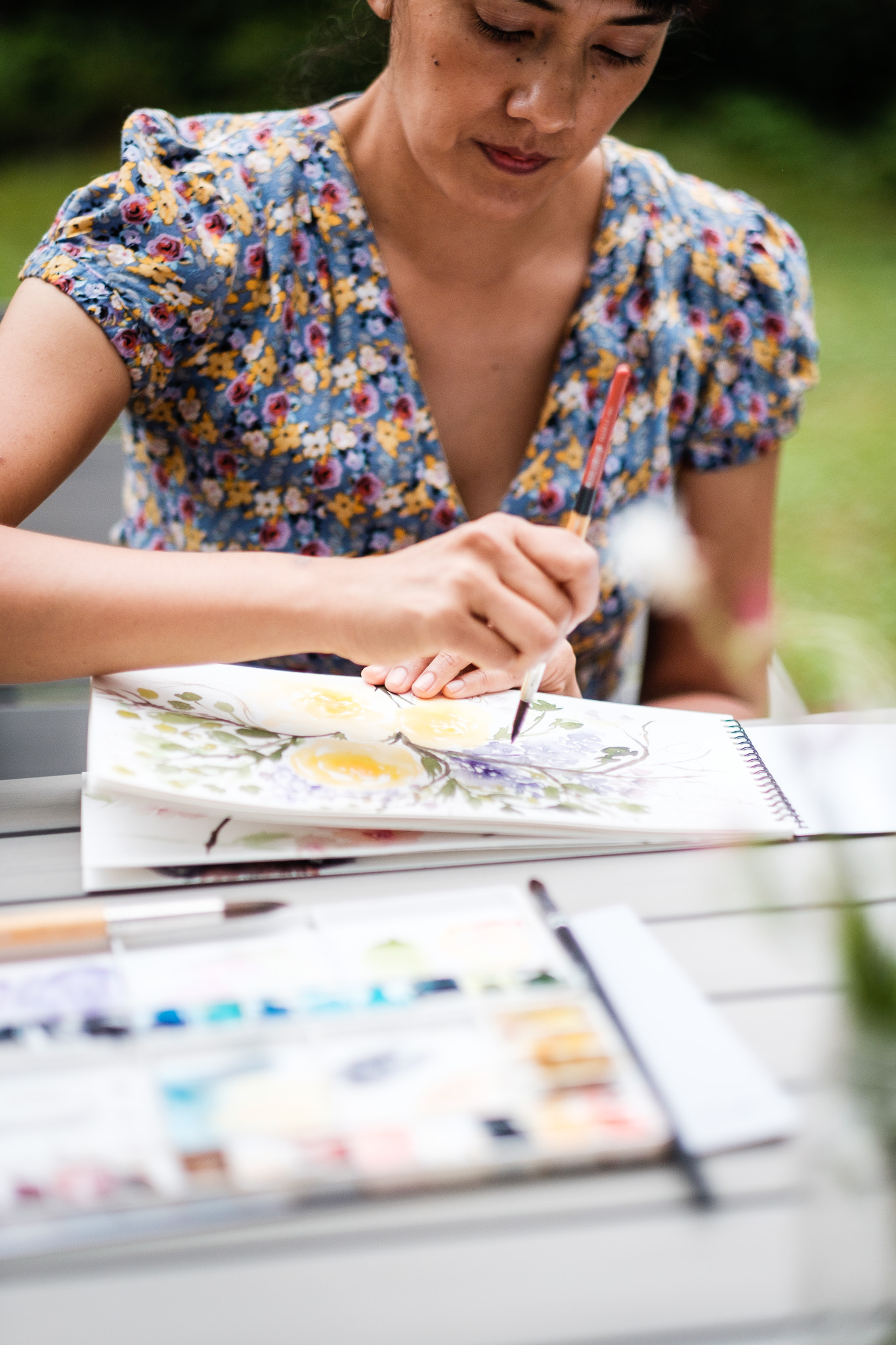 Female watercolor artist in Montreal, paints outdoors in her backyard as part of a personal branding photo session.
