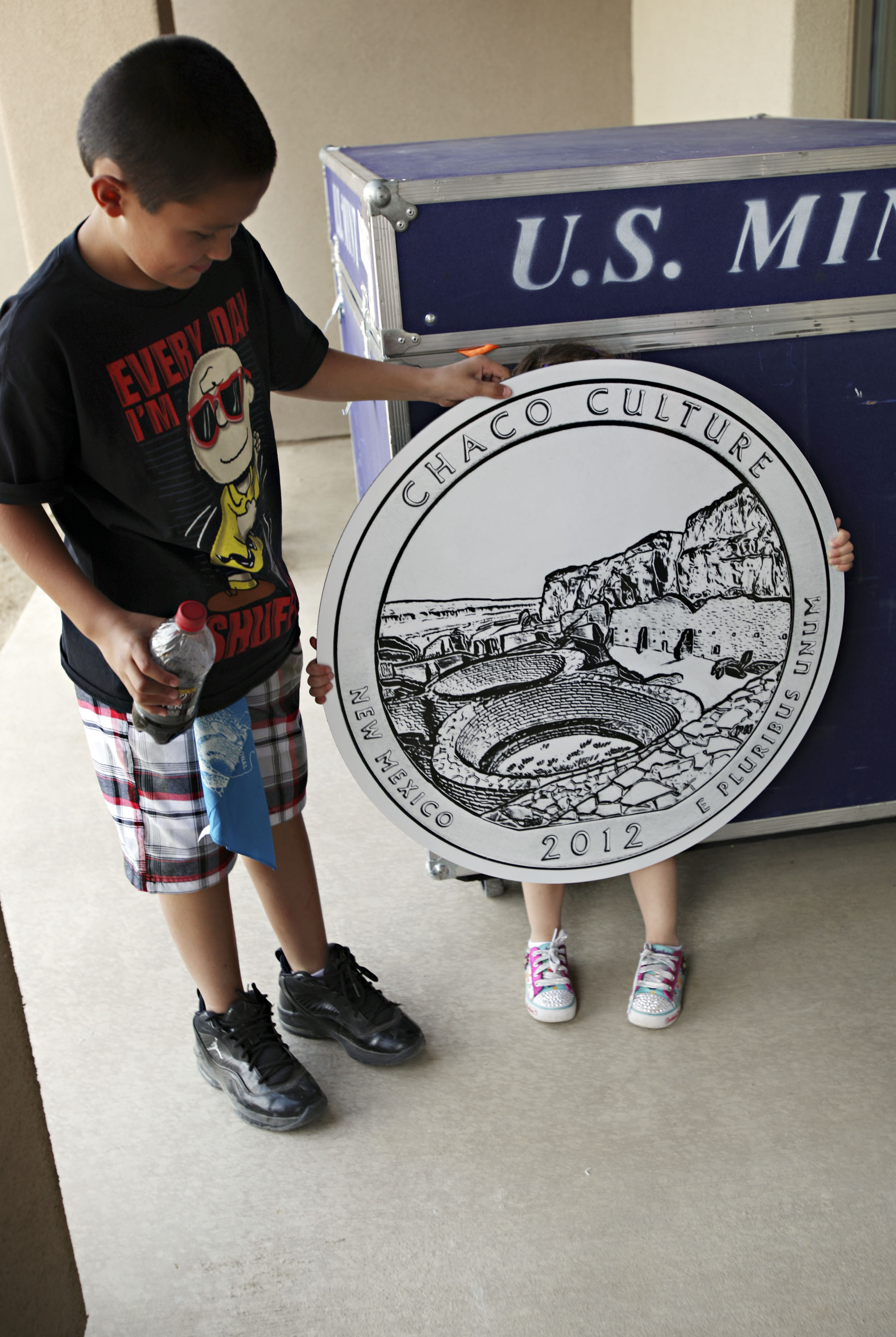 Peyton Gallegos, 3, hides behind the Chaco Canyon quarter prop after posing for a photo with her brother, Timothy Gallegos, 11, after the official quarter launch at Chaco Canyon, Thursday, April 26, 2012. The children were visiting with their mother, Denise Gallegos from Chama. (Morgan Petroski/Albuquerque Journal)