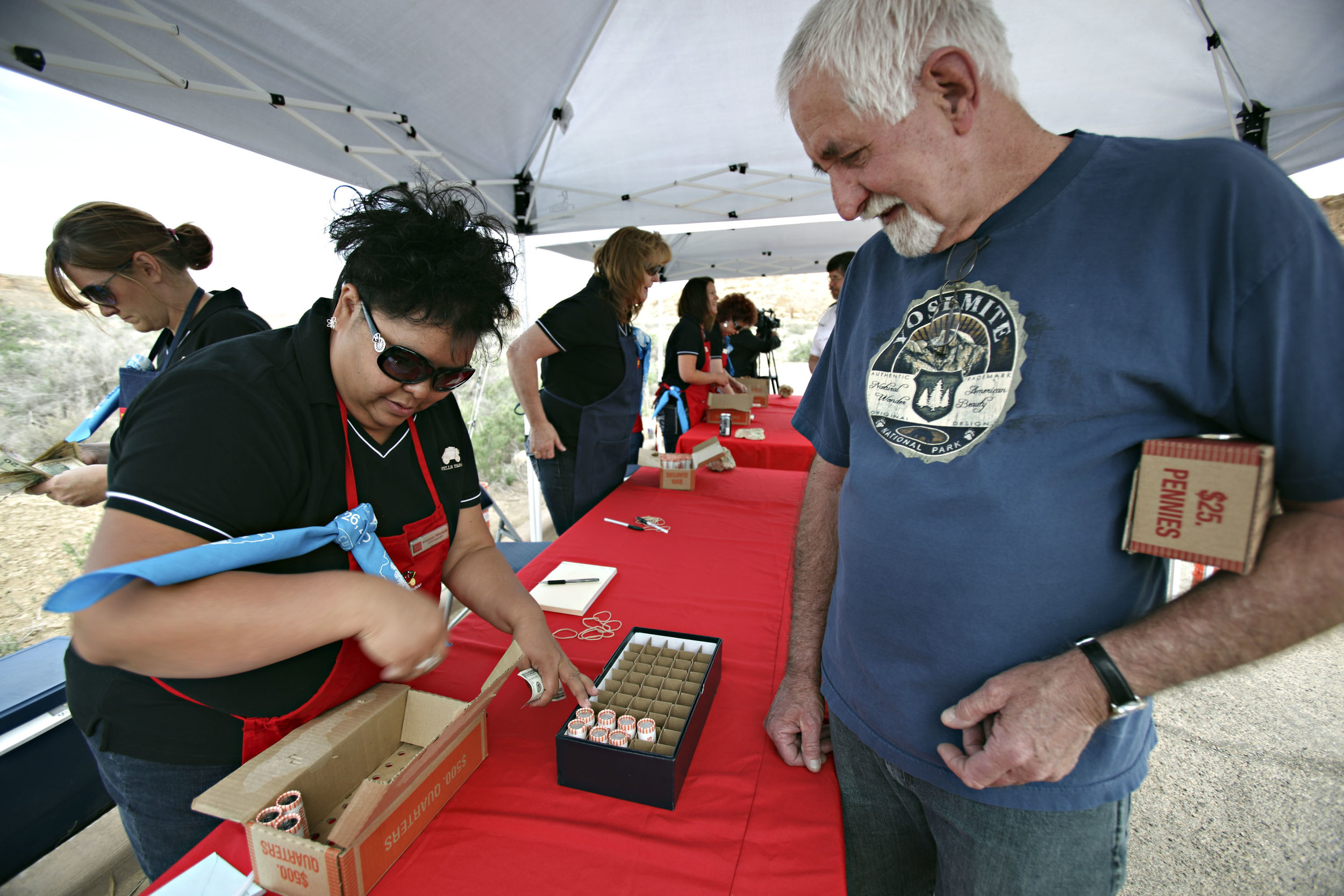 Gallup Wells Fargo store manager Melanie Mitchell exchanges 10 rolls of $10 quarters for coin collector Jon Brackin, from Las Vegas, Nevada, during the quarter launch at Chaco Canyon, Thursday, April 26, 2012. Brackin said he has been to 6 of the 8 America the Beautiful quarter launches so far. Wells Fargo brought an armored car out with the new quarters. (Morgan Petroski/Albuquerque Journal)