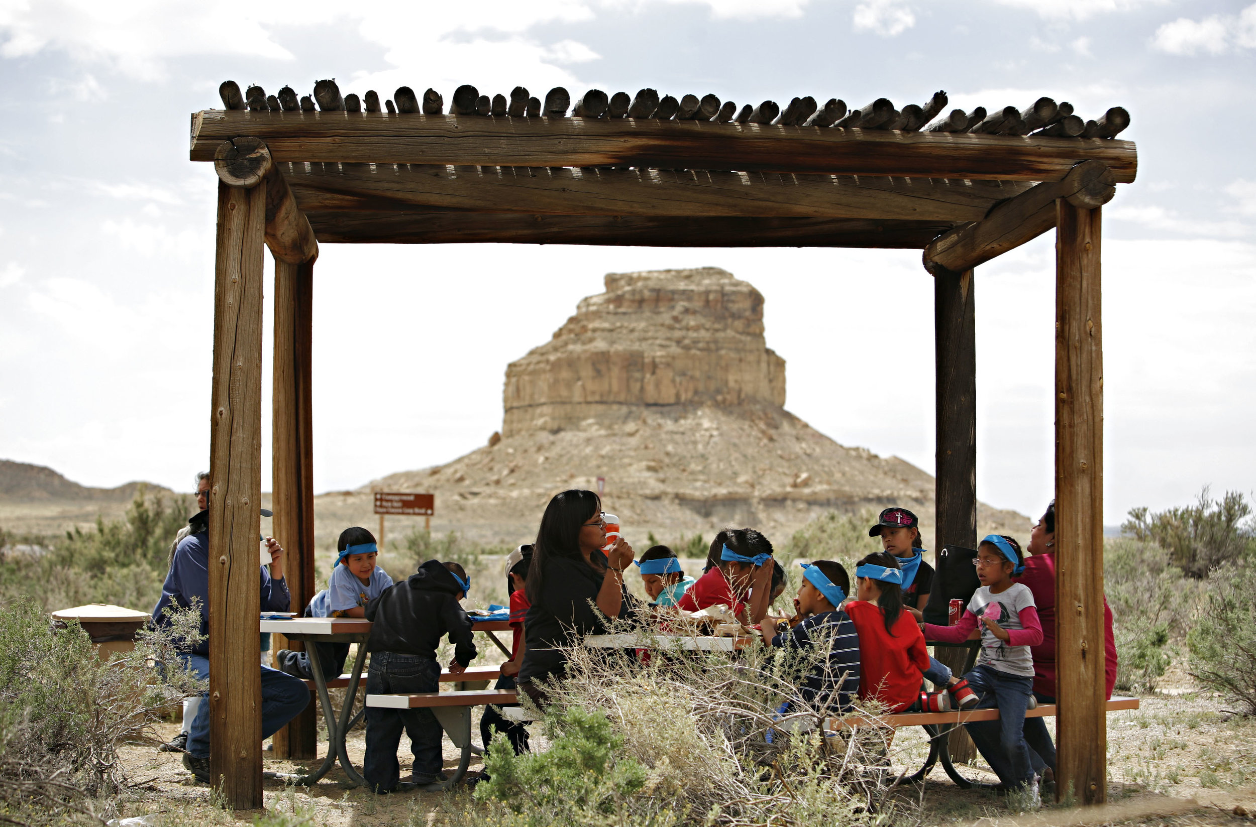 Children from Hanaa'dli Community School eat lunch outside the new visitor center at Chaco Canyon and in front of Fajada Butte, Thursday, April 26, 2012. (Morgan Petroski/Albuquerque Journal)