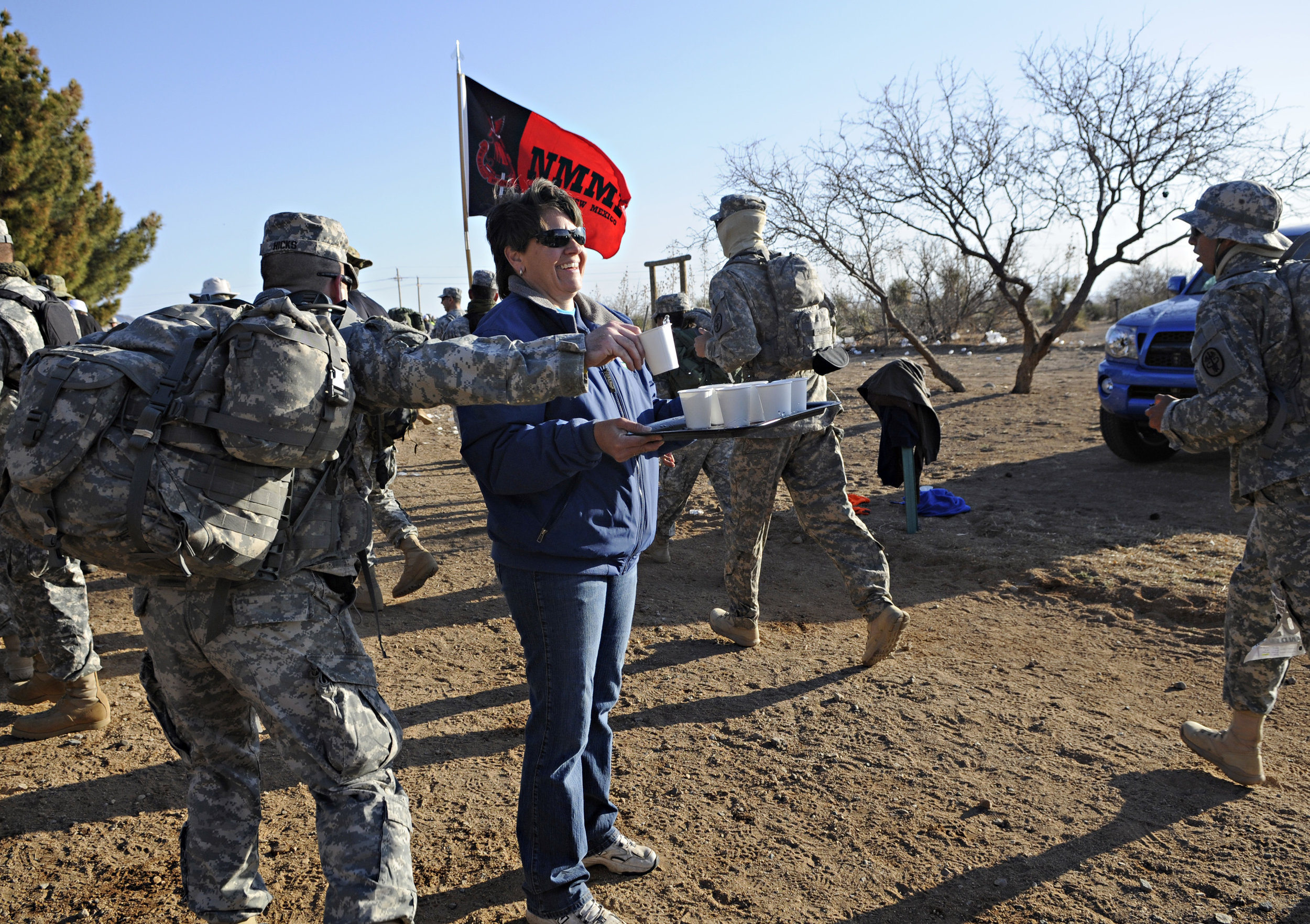 Volunteer Vicki Anderson, from Las Cruces, holds out water for the walkers and runners during the 22nd Annual Bataan Memorial Death March at White Sands Missile Range, Sunday, March 27, 2011. (Morgan Petroski/Albuquerque Journal)