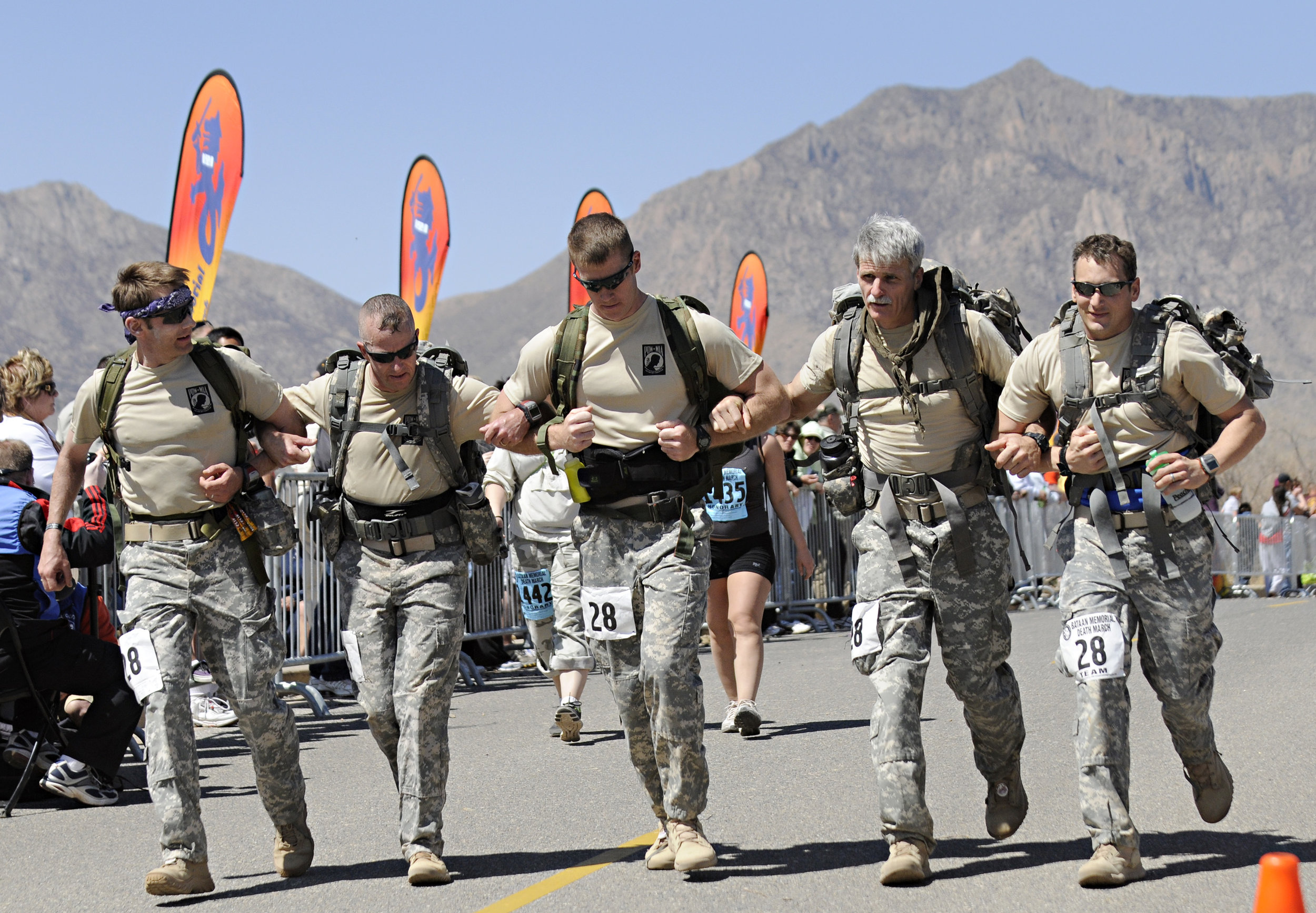 A team prepares to cross the finish line of their 26.2-mile run arm in arm during the 22nd Annual Bataan Memorial Death March at White Sands Missile Range, Sunday, March 27, 2011. (Morgan Petroski/Albuquerque Journal)