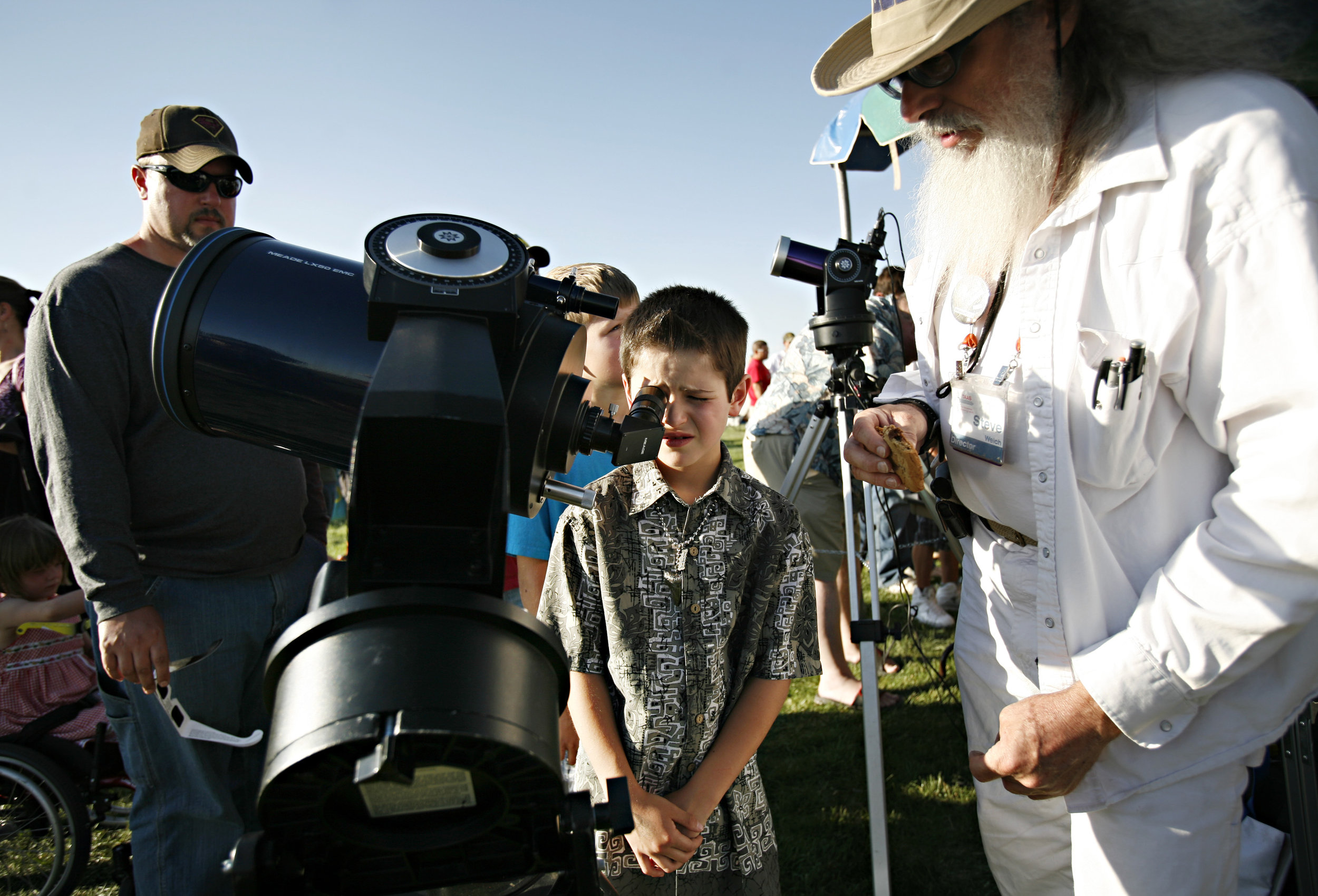 Xavier Martin, 8, looks at the sun through a telescope manned by TAAS member Steve Welch, at right, during the annular solar eclipse viewing party near the Hard Rock Casino Presents the Pavilion, Sunday, May 20, 2012, in Albuquerque, NM. (Morgan Petroski/Albuquerque Journal)