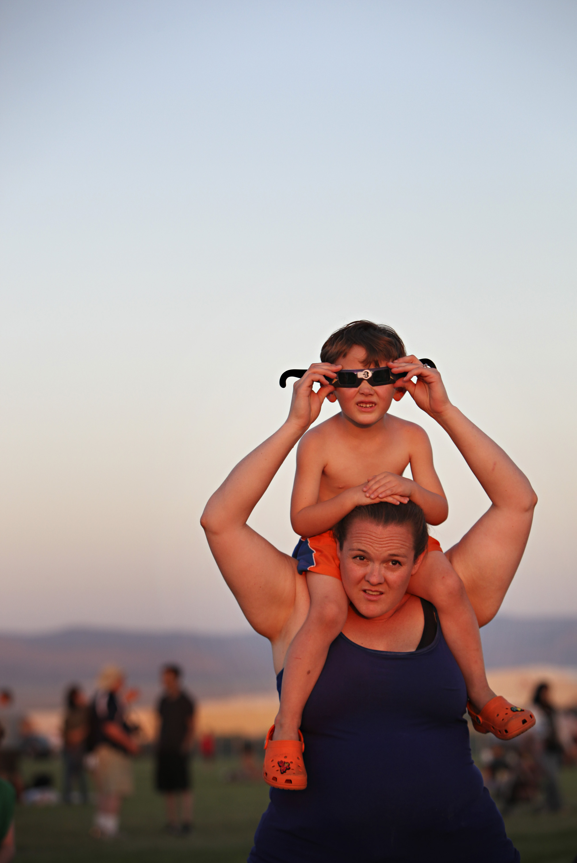 Jaxon Wright, 4, looks at the annular solar eclipse through special glasses while sitting on his mother, Tiffany Wright's, shoulders during the viewing party near the Hard Rock Casino Presents the Pavilion, Sunday, May 20, 2012, in Albuquerque, NM. (Morgan Petroski/Albuquerque Journal)