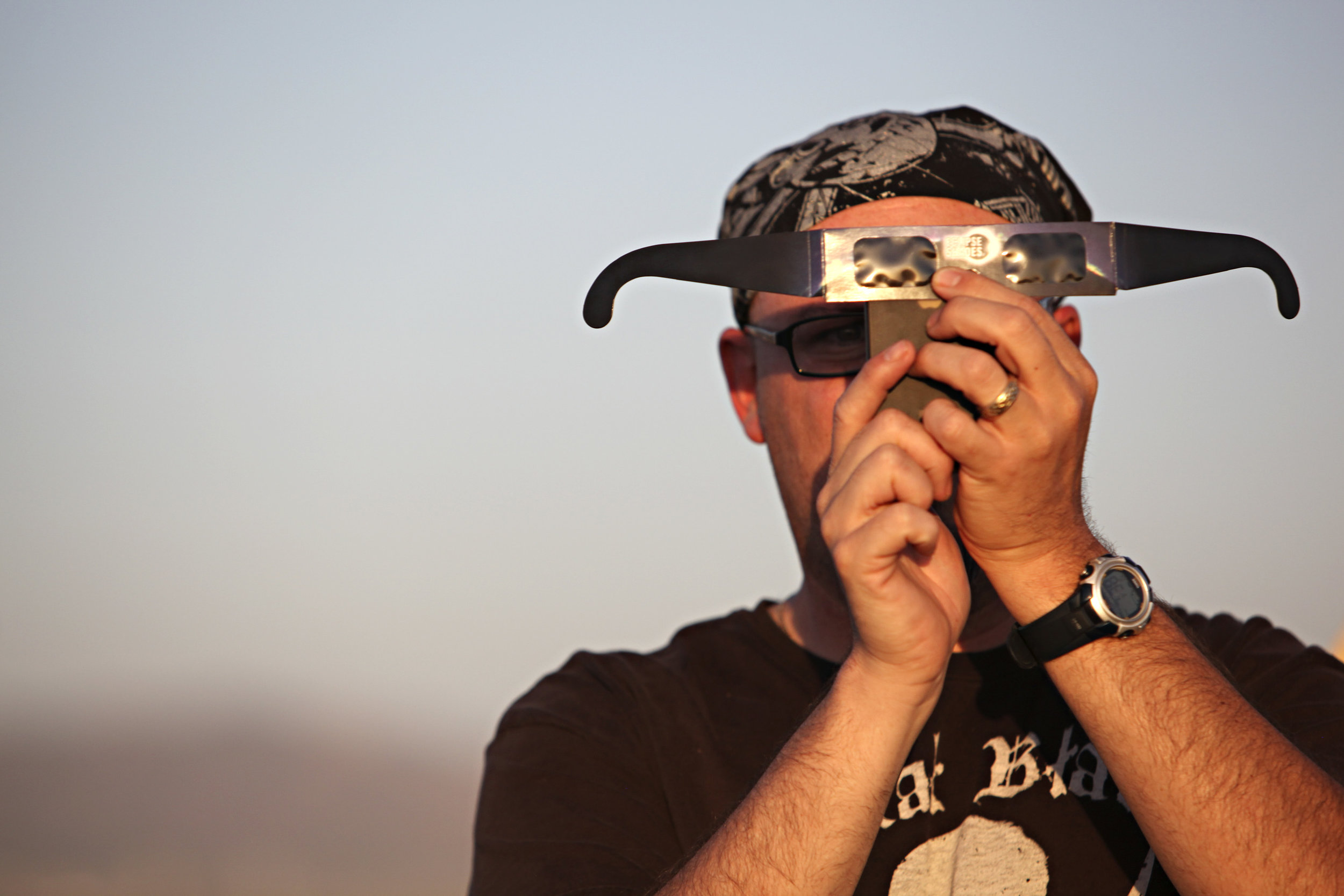 John Converse, of Albuquerque, takes a cell phone photo of the annular solar eclipse through the lens of a pair of solar glasses during the eclipse viewing party near the Hard Rock Casino Presents the Pavilion, Sunday, May 20, 2012, in Albuquerque, NM. (Morgan Petroski/Albuquerque Journal)