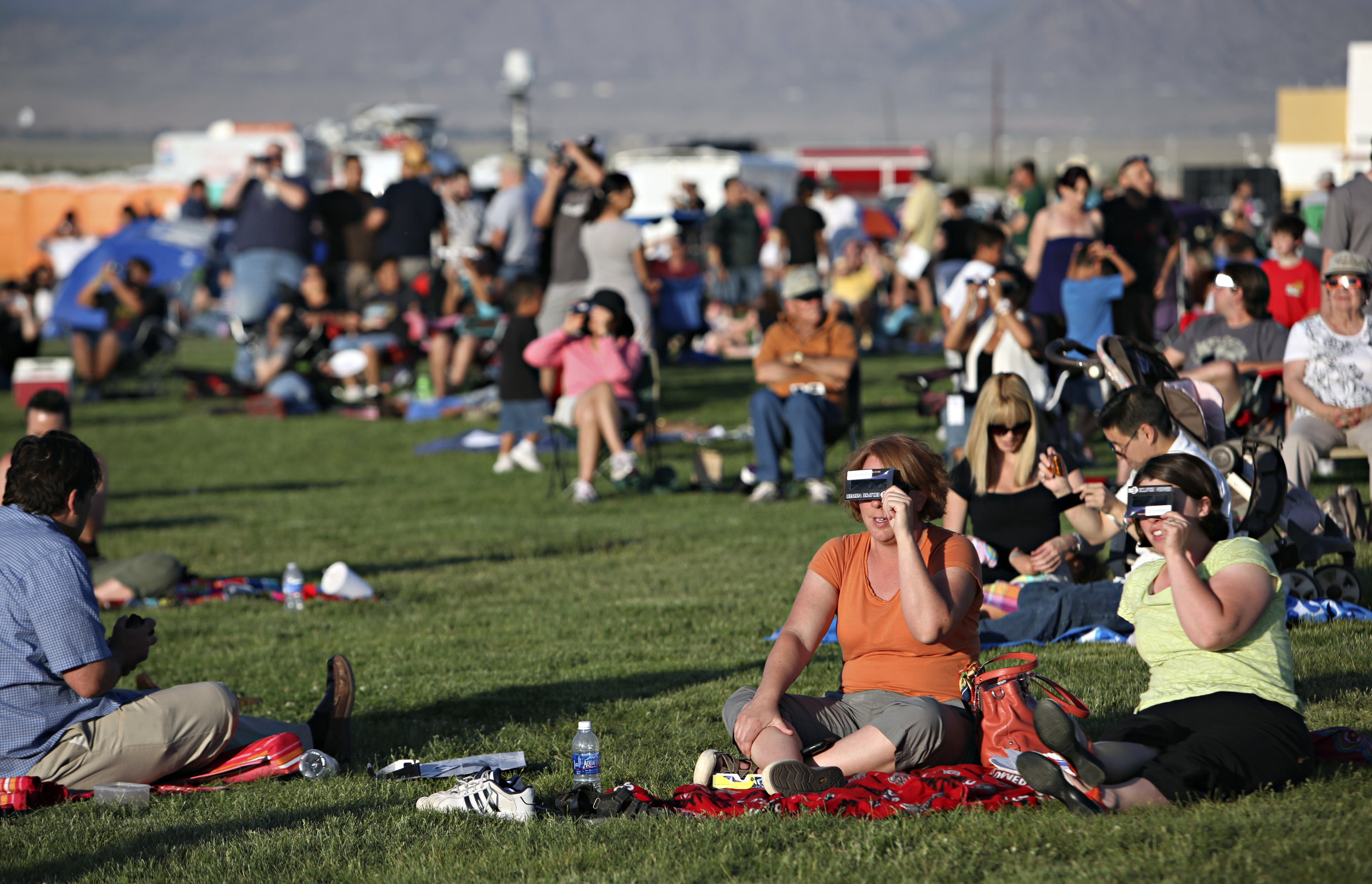 From right, Deanna Creighton and Crystal Humble, both from Albuquerque, watch the annular solar eclipse during the eclipse viewing party near the Hard Rock Casino Presents the Pavilion, Sunday, May 20, 2012, in Albuquerque, NM. (Morgan Petroski/Albuquerque Journal)