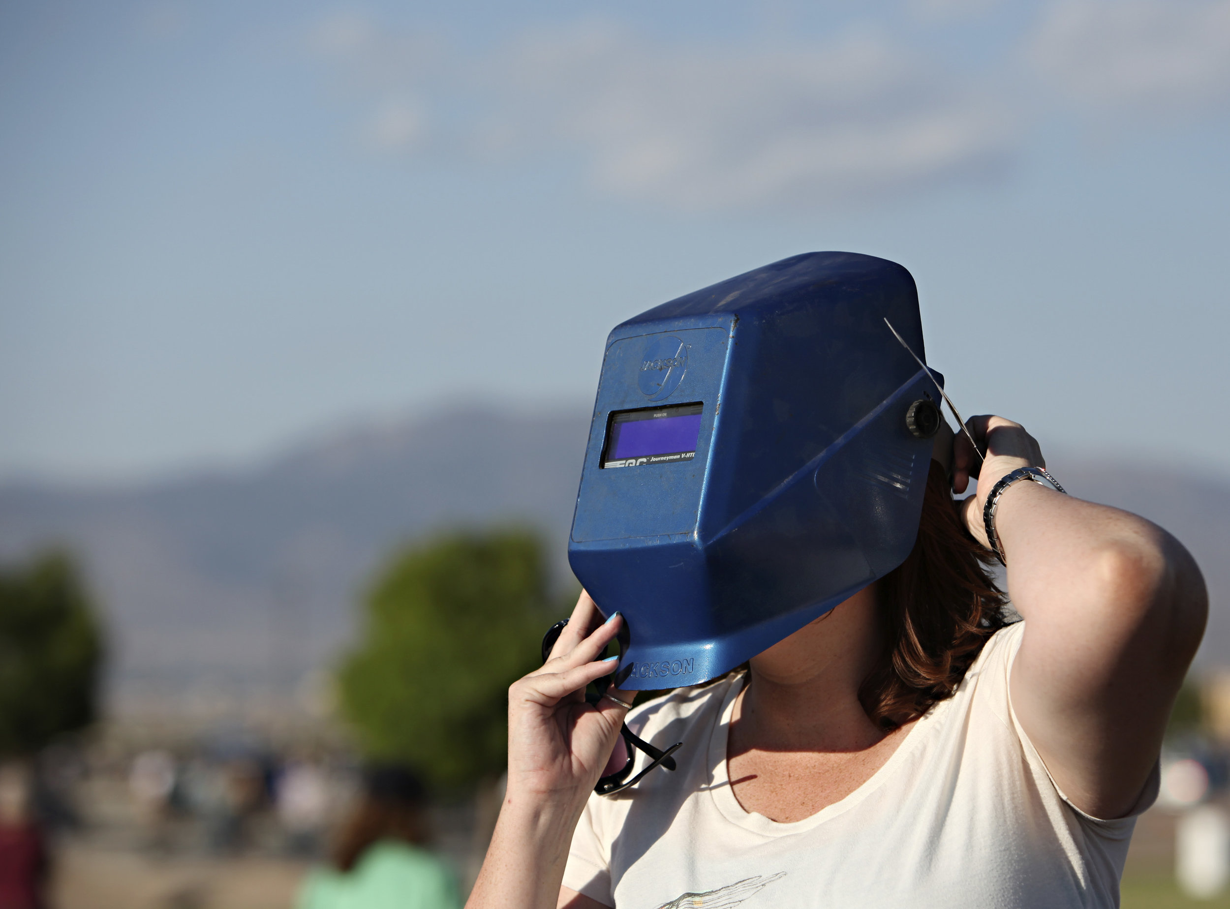 Karen Converse, from Albuquerque, watches the annular solar eclipse through a welder's helmet during the eclipse viewing party near the Hard Rock Casino Presents the Pavilion, Sunday, May 20, 2012, in Albuquerque, NM. (Morgan Petroski/Albuquerque Journal)