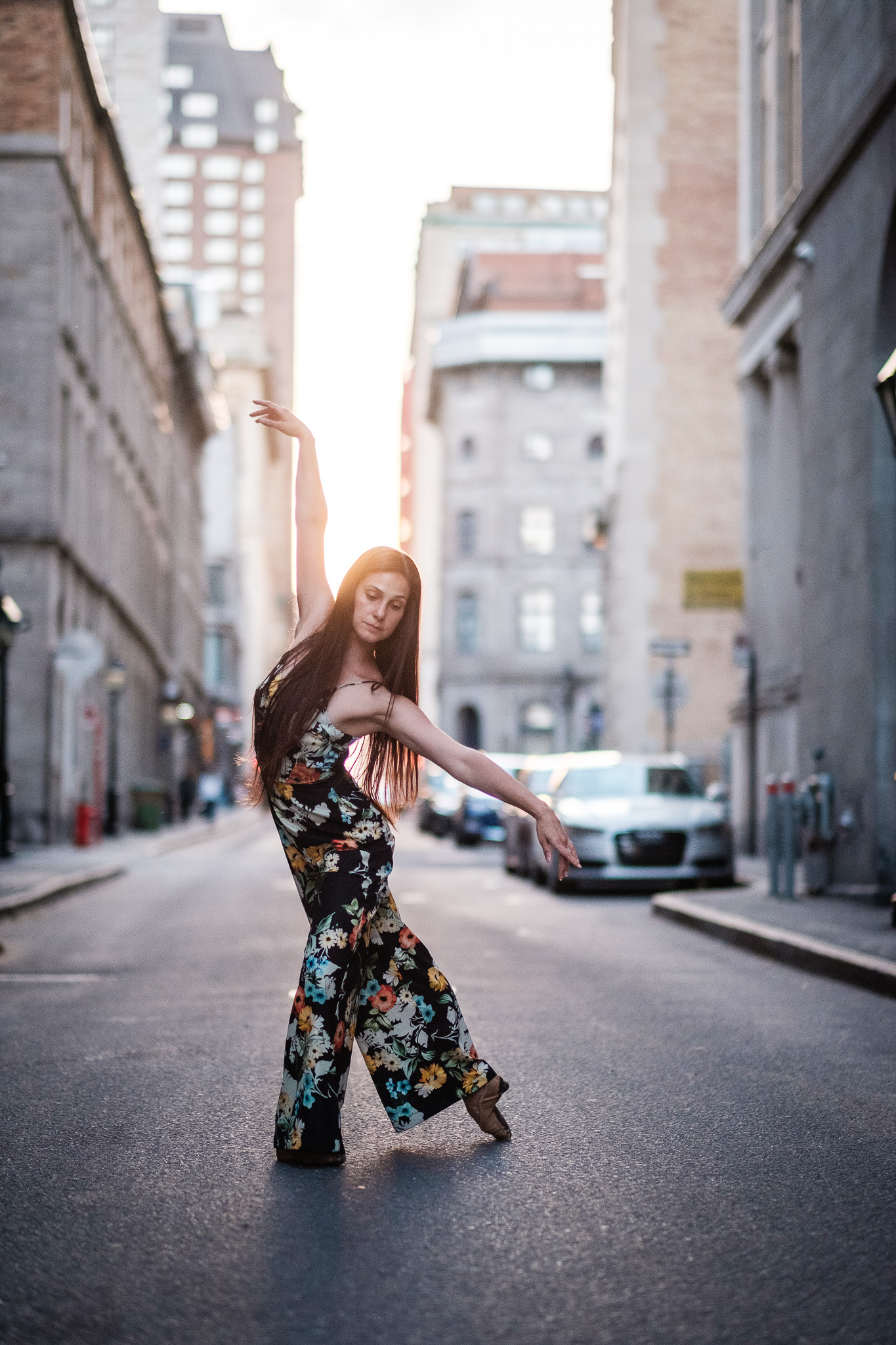 ballet dancer in middle of city street with sun setting behind her in montreal