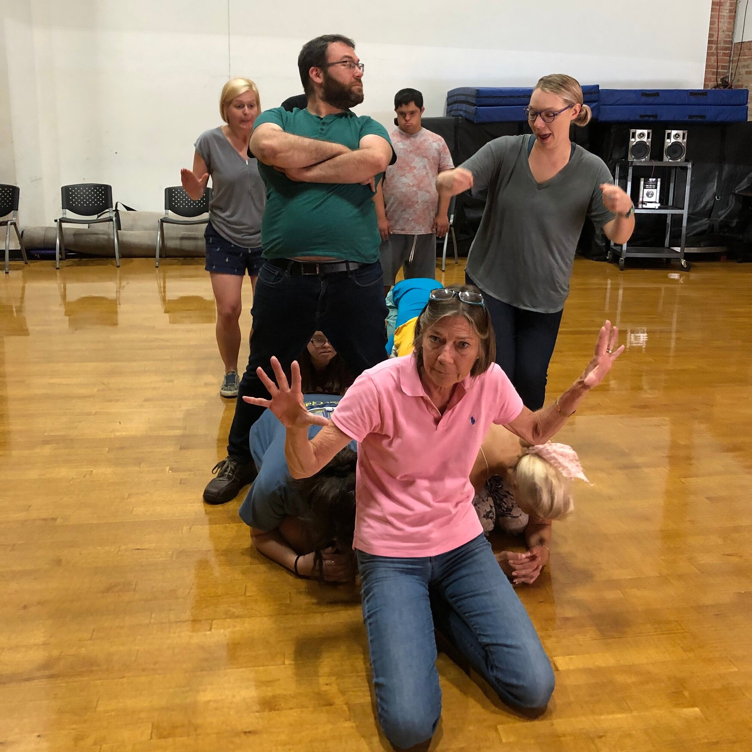 Image description:  actors, facilitators, and A.B.L.E. parents play the game Stage Pictures in the Tuesday ensemble orientation. This group is working as a team and using their bodies to make a picture of a car.