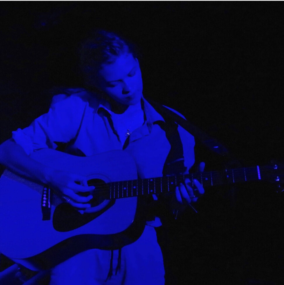 Image description: The multi-talented Kiaran stands playing a guitar washed in a blue spotlight.