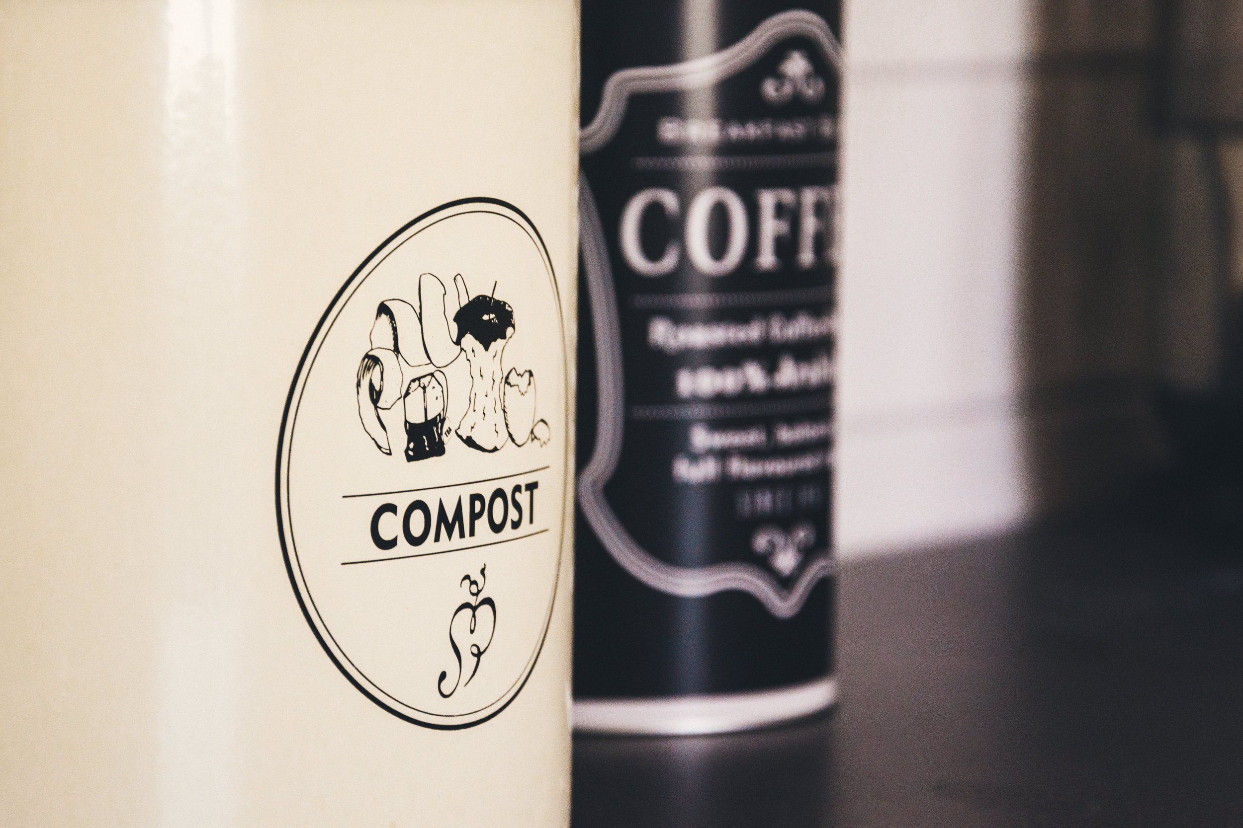 Ivory compost pail beside coffee canister.