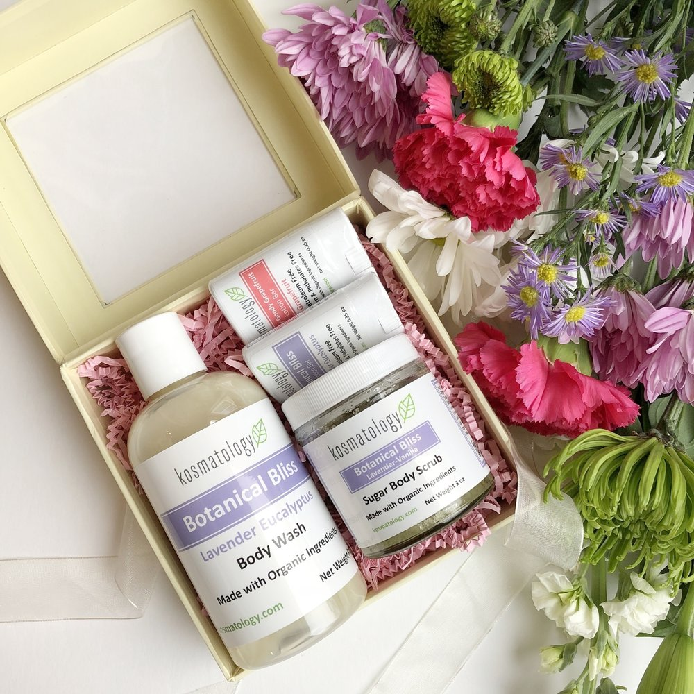 Gift set featuring a body wash, sugar body scrub and two mini lotion bars in a box beside a bouquet of flowers.