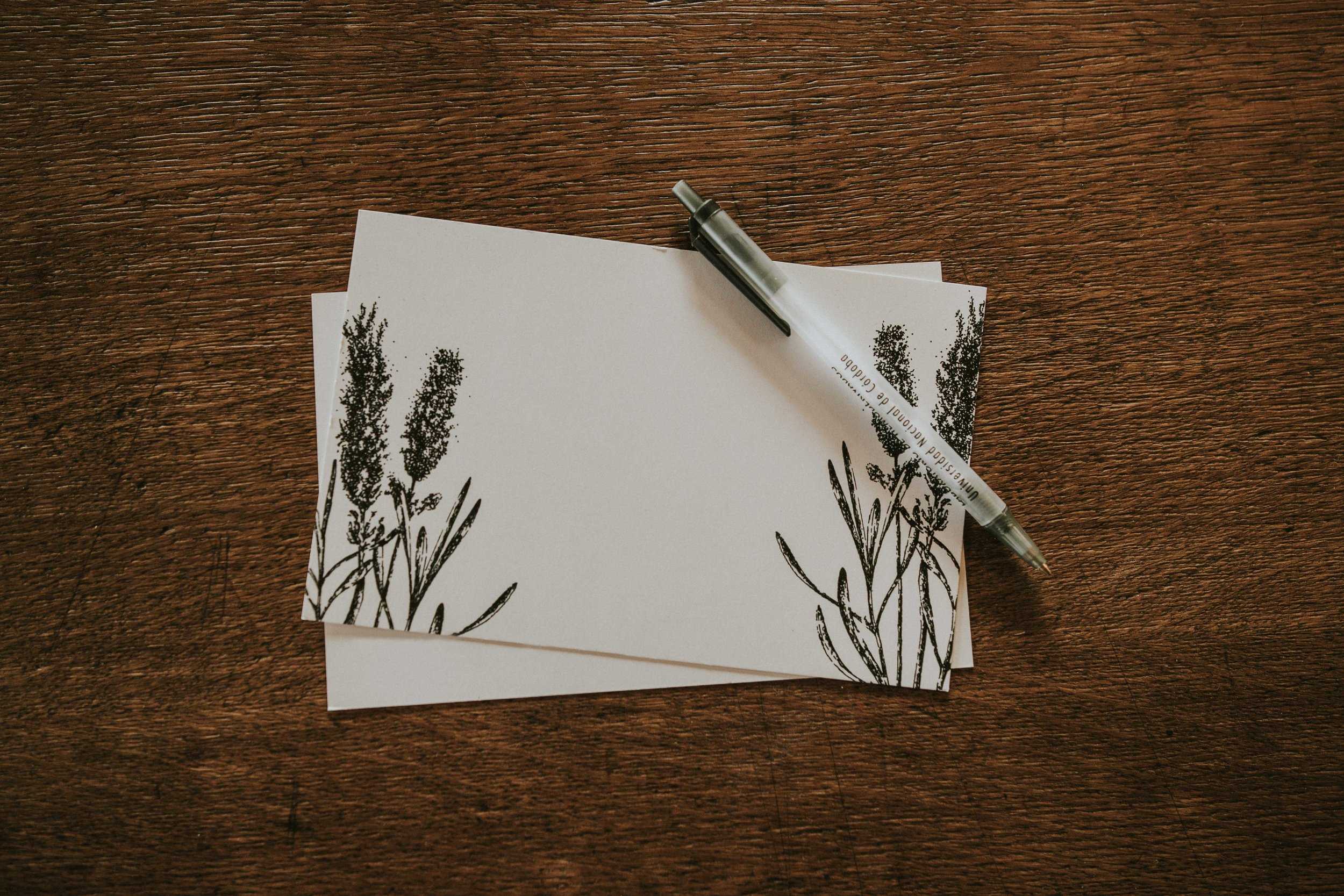 Blank card with floral design and pen sitting on a wooden desk.